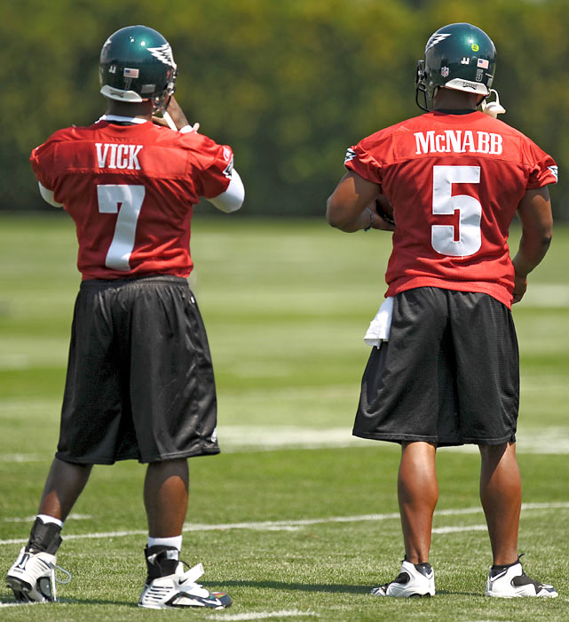 Newly acquired quarterback Michael Vick speaks with veteran Donovan McNabb  during training camp in Philadelphia.