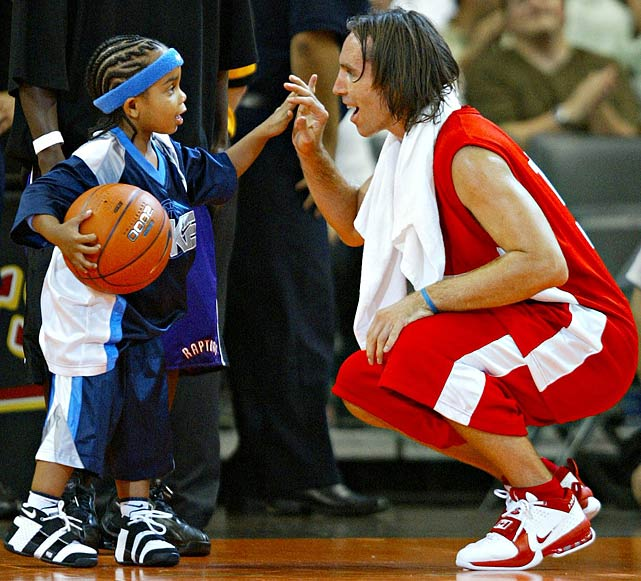 Nash squats to high-five one of his young admirers during a charity basketball event in 2005.  He continues to be a fan-favorite, as he's been named to the All-Star Game seven times throughout his professional career.