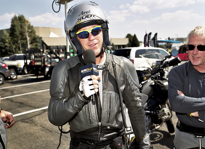 Covering a cycling race takes a special set of skills, being able to provide insightful commentary while seated on the back of a speeding motorcycle is high on the list.