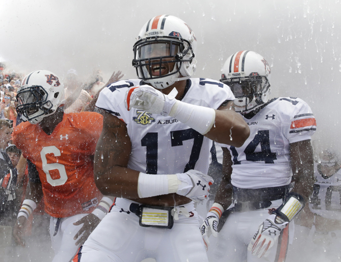 Auburn quarterback's Jeremy Johnson (6) Ben Durand (17) and defensive back Stephen Roberts (14) run out onto the field before their spring NCAA college football game, Saturday, April 18, 2015, in Auburn, Ala.