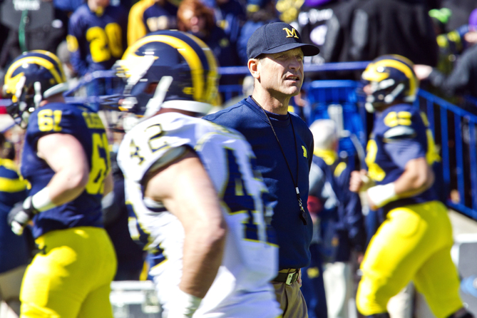 Michigan head coach Jim Harbaugh watches his players as they warm up before a spring NCAA college football game in Ann Arbor, Mich., Saturday, April 4, 2015.