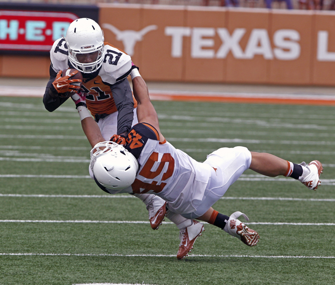 Texas running back Duke Catalon (21) runs against defensive back Kyle Ashby (45) during the first quarter of Texas' Orange and White spring NCAA college football game, Saturday, April 18, 2015, in Austin, Texas.