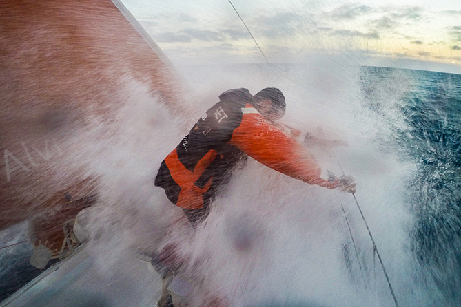 November 06, 2014. Leg 1 onboard Team Alvimedica. Day 26. The final 100 miles of Leg 1 prove to be the hardest on the heavy-air sprint into Cape Town. Seb Marsset takes a wave to the chest during a sunset sail change.