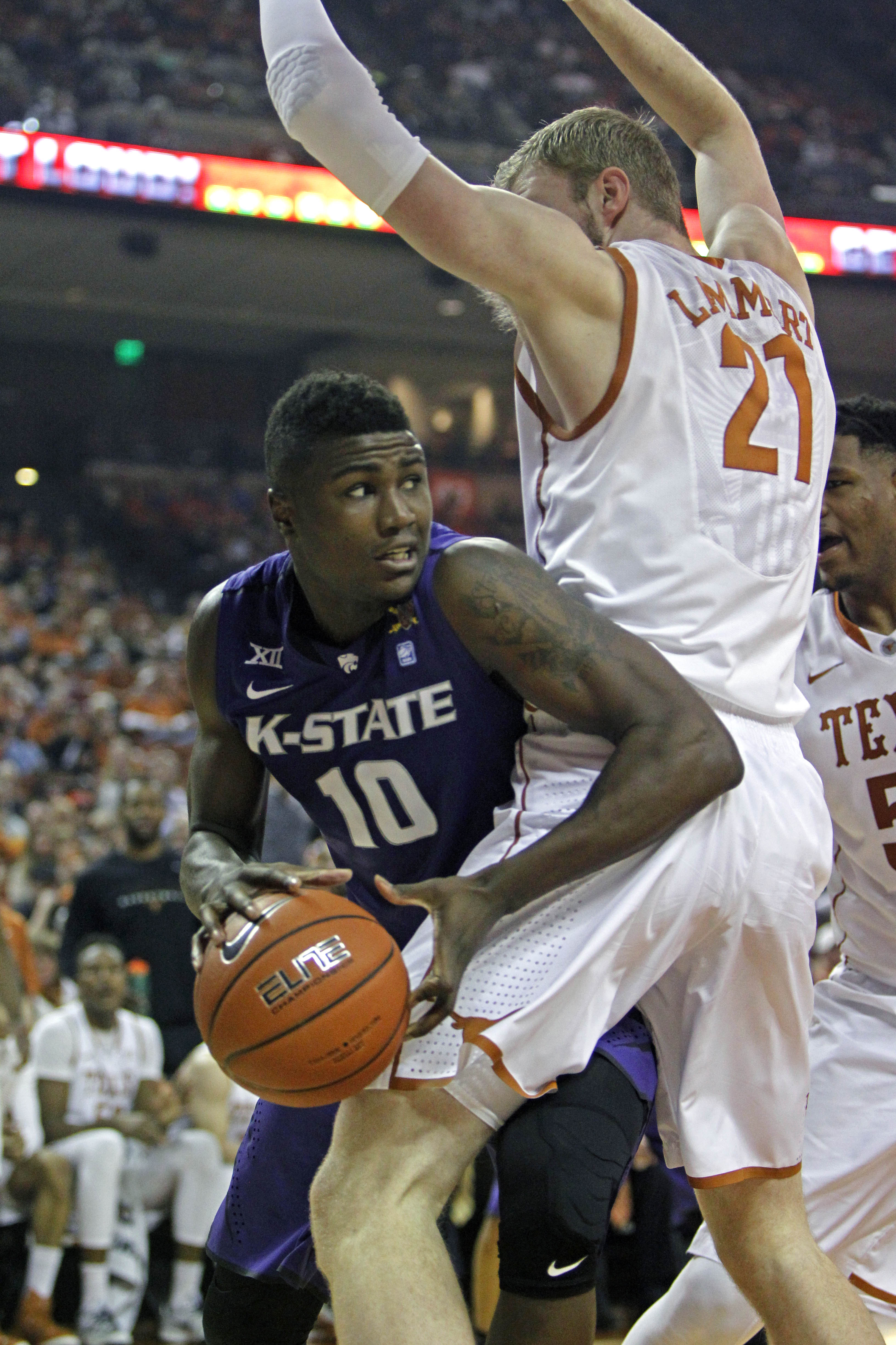 Kansas State forward Malek Harris (10) looks to pass around Texas forward Connor Lammert (21) during the first half of an NCAA college basketball game, Saturday, March 7, 2015, in Austin, Texas.  (AP Photo/Michael Thomas)