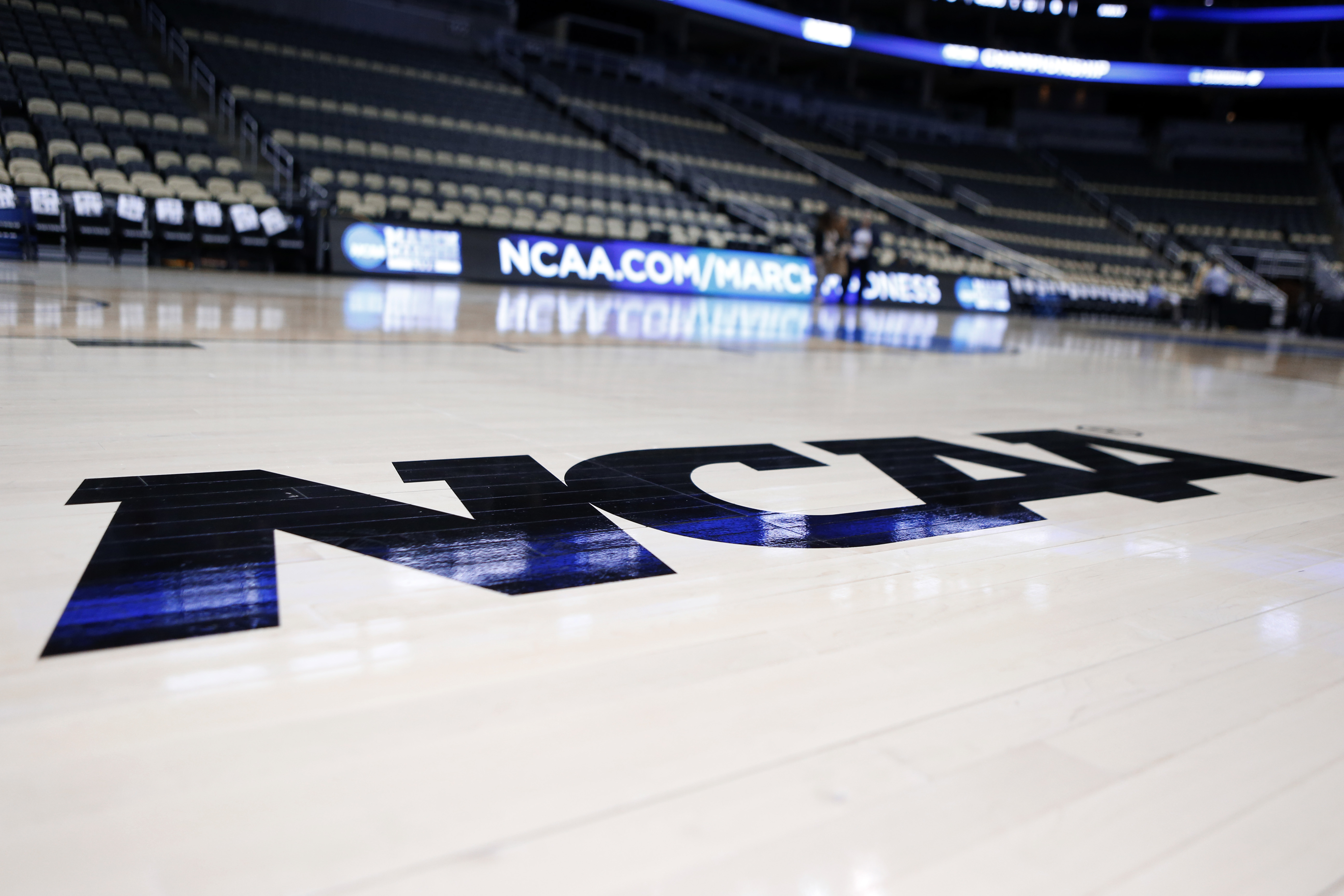 The NCAA logo is on the court as work continues at The Consol Energy Center in Pittsburgh, Wednesday, March 18, 2015, for the NCAA college basketball second and third round game. Second round games start on Thursday. (AP Photo/Keith Srakocic)
