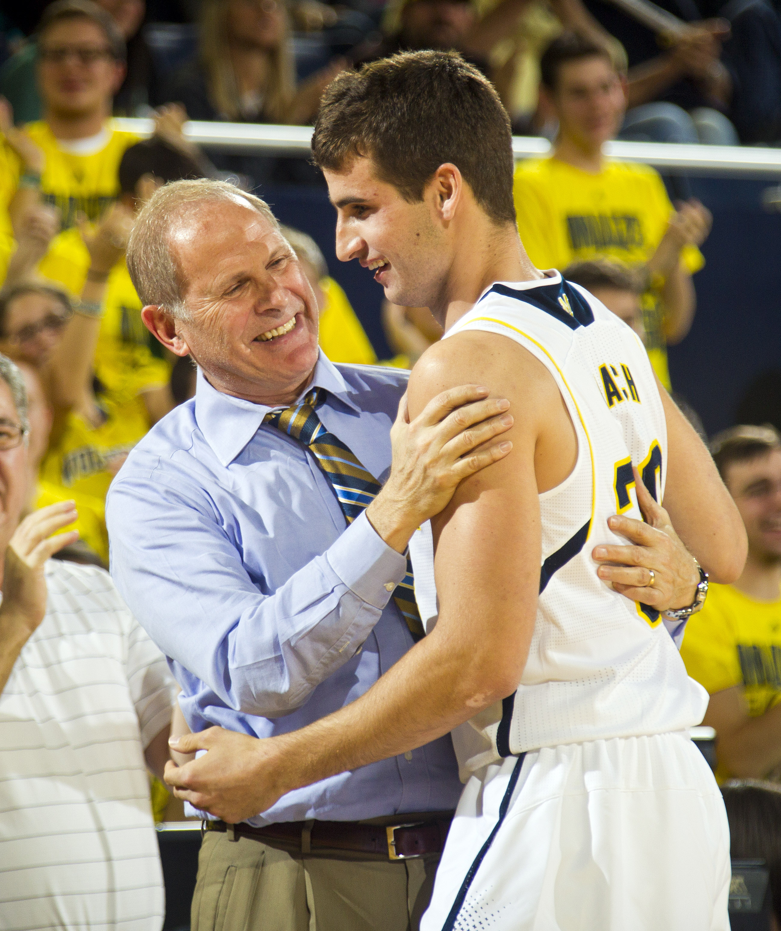 Michigan head coach John Beilein congratulates guard Austin Hatch after he made a free throw basket in the second half of an NCAA college basketball exhibition game against Wayne State at Crisler Center in Ann Arbor, Mich., Monday, Nov. 10, 2014. Michigan