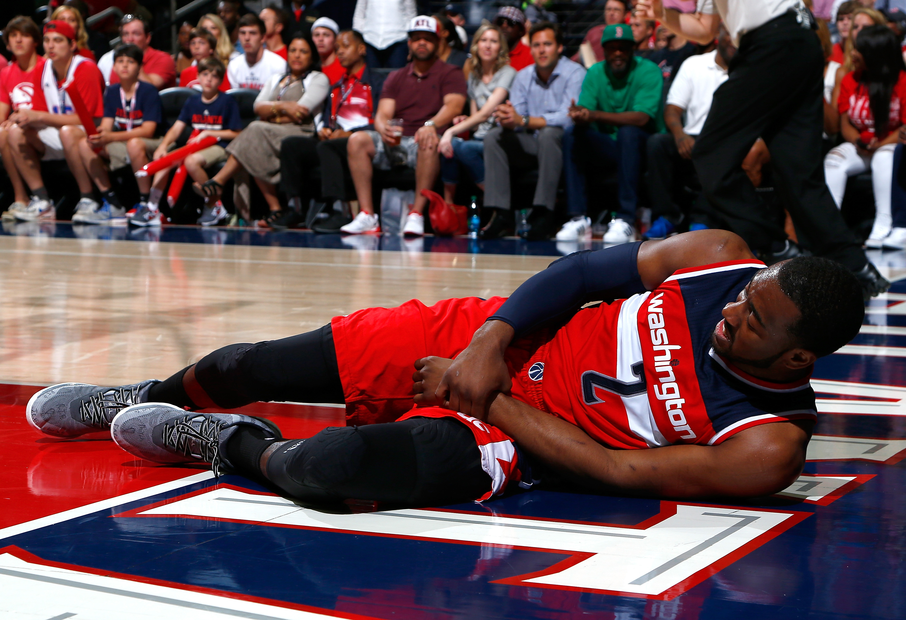 ATLANTA, GA - MAY 03:  John Wall #2 of the Washington Wizards grabs his wrist after missing a basket and landing on the floor against the Atlanta Hawks during Game One of the Eastern Conference Semifinals of the 2015 NBA Playoffs at Philips Arena on May 3