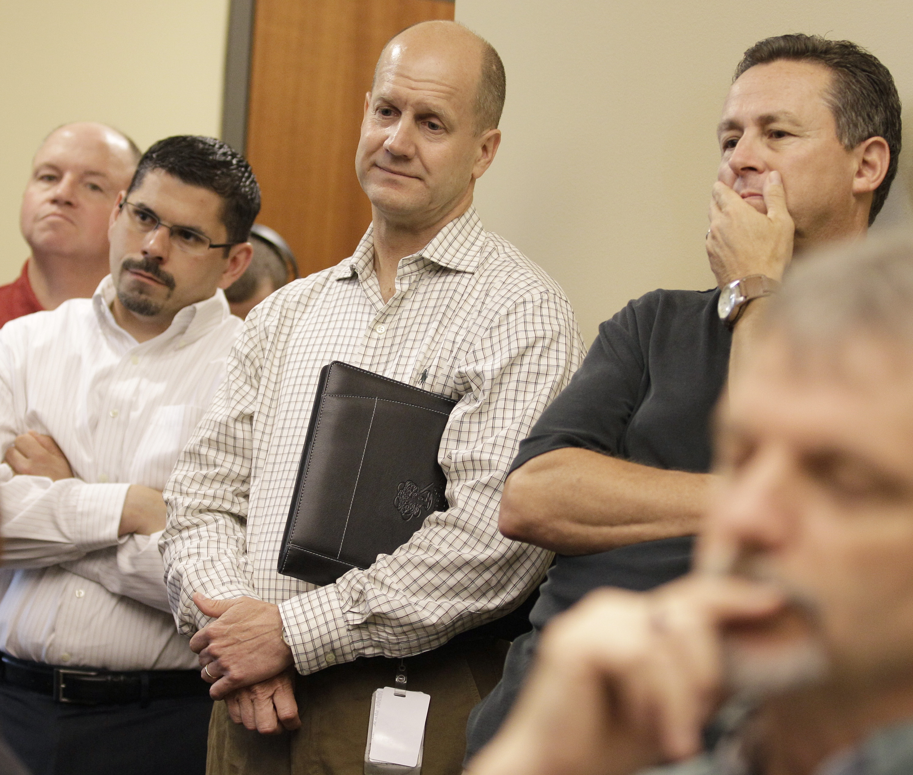 FILE - In this July 9, 2010, file photo, President of the Cleveland Cavaliers and Quicken Loans Arena Len Komorowski, center, listens in as team general manager Chris Grant and head coach Byron Scott speak to the media in Independence, Ohio. On the sports