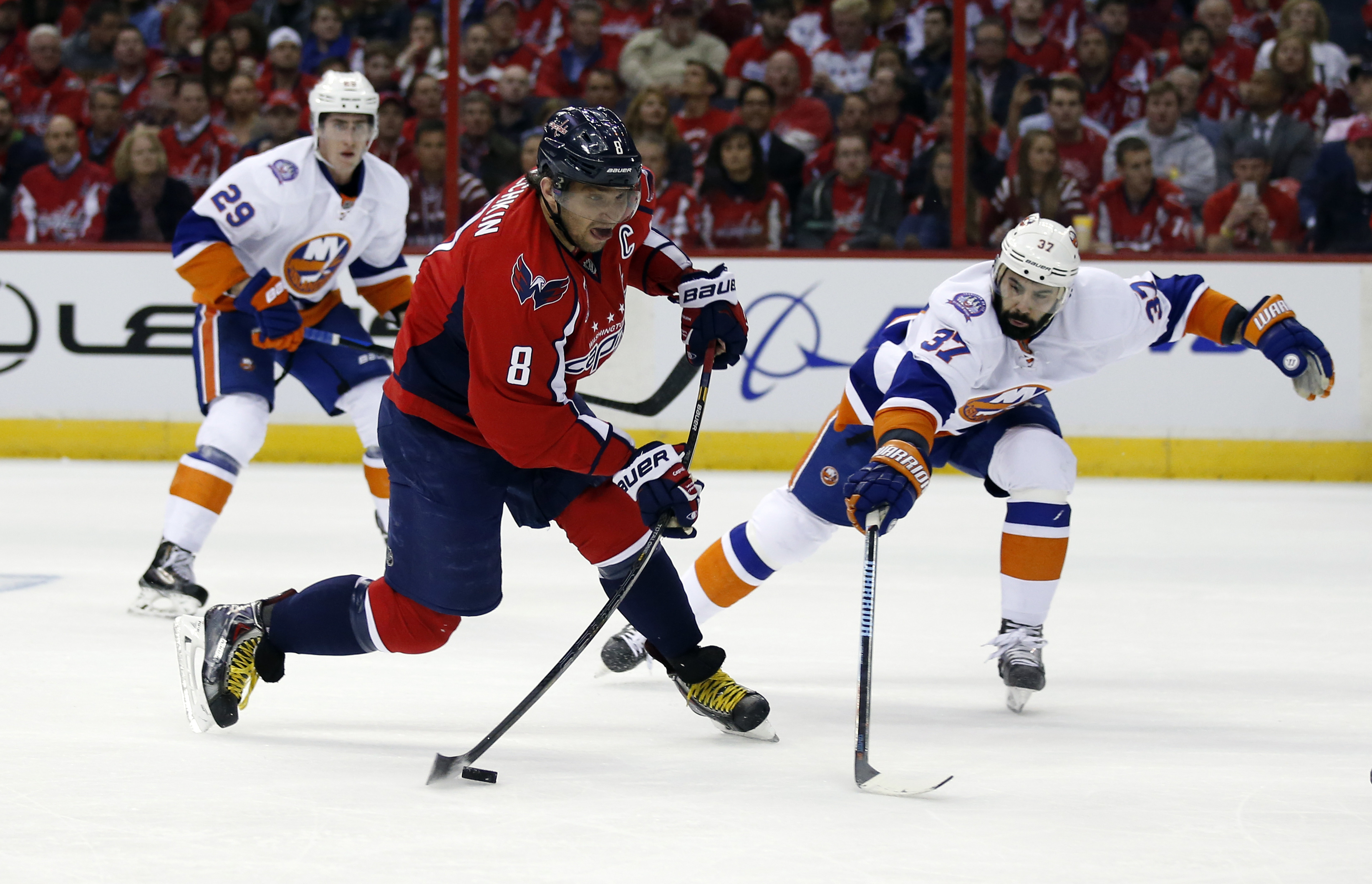 Washington Capitals left wing Alex Ovechkin (8), from Russia, shoots past New York Islanders defenseman Brian Strait (37) during the first period of Game 1 of a first-round NHL hockey Stanley Cup playoffs series, Wednesday, April 15, 2015, in Washington.