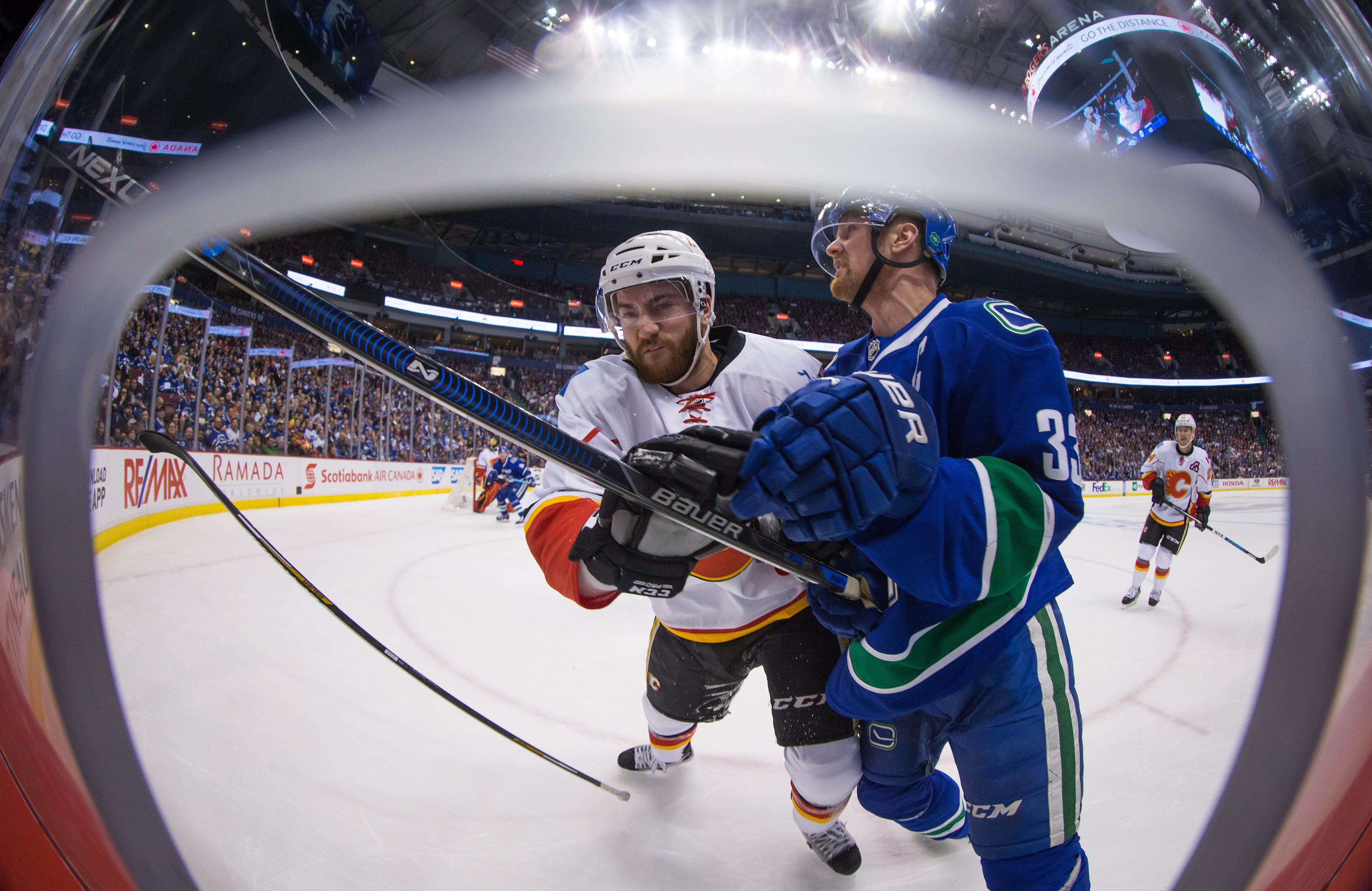 Calgary Flames' T.J. Brodie, back, loses his stick as he checks Vancouver Canucks' Henrik Sedin, of Sweden, during the first period of Game 1 of an NHL hockey first-round playoff series, Wednesday, April 15, 2015, in Vancouver, British Columbia. (Darryl D