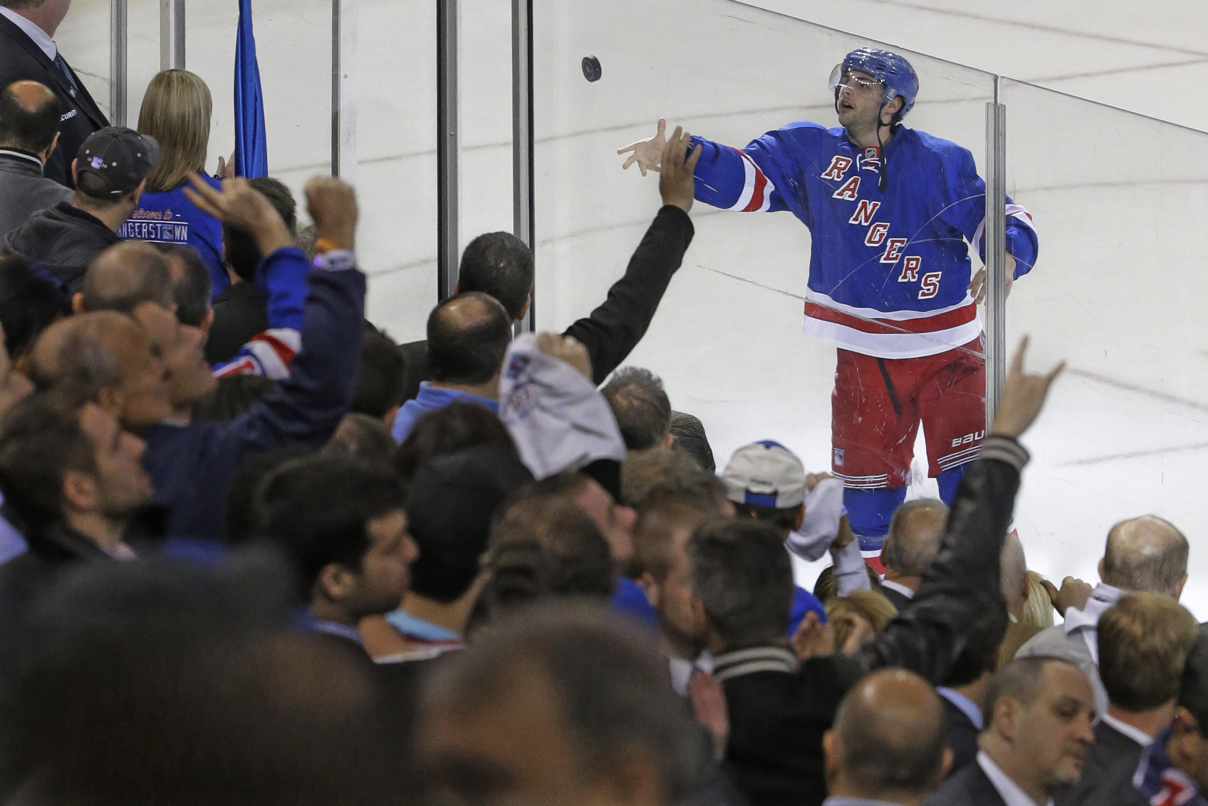 New York Rangers center Derick Brassard tosses the puck to fans after being named the game's most valuable player at the end of Game 1 in the first round of the NHL hockey Stanley Cup playoffs against against the Pittsburgh Penguins, Thursday, April 16, 2