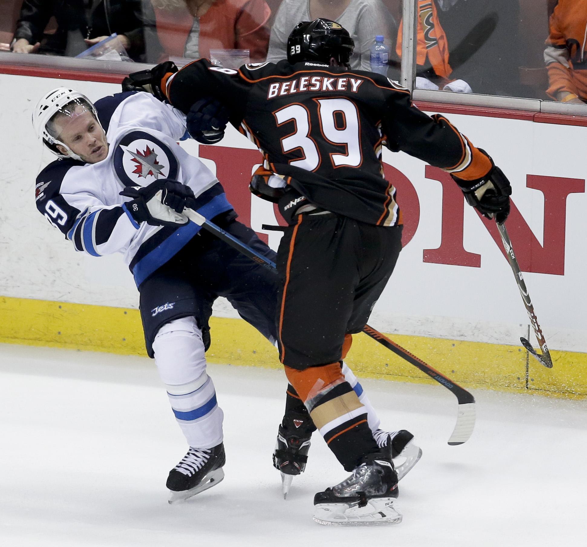 Anaheim Ducks left wing Matt Beleskey, right, checks Winnipeg Jets defenseman Tobias Enstrom during the second period of Game 1 of a first-round NHL hockey playoff series in Anaheim, Calif., Thursday, April 16, 2015. (AP Photo/Chris Carlson)