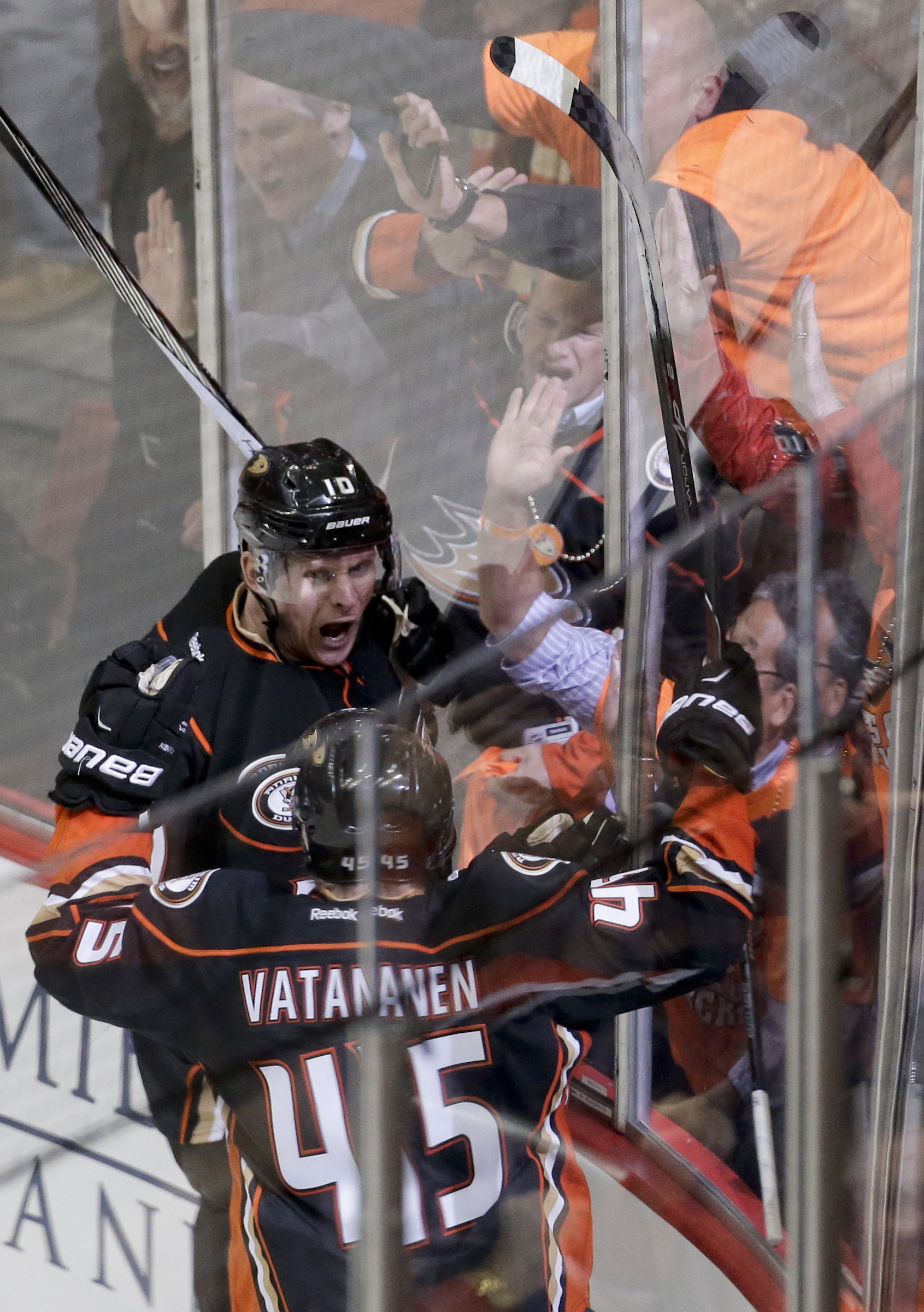 Anaheim Ducks right wing Corey Perry, top, celebrates his first goal with defenseman Sami Vatanen against the Winnipeg Jets during the third period of Game 1 of a first-round NHL hockey playoff series in Anaheim, Calif., Thursday, April 16, 2015. (AP Phot