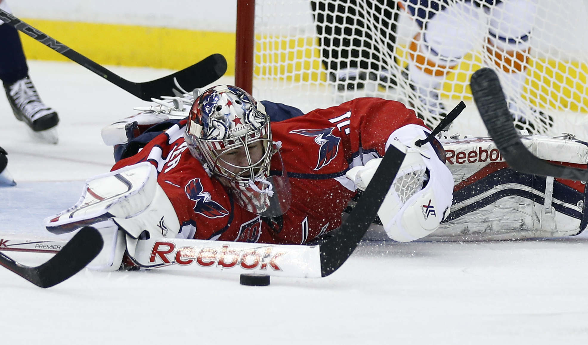 against the Washington Capitals goalie Philipp Grubauer, from Germany, lunges to knock the puck away during the second period of Game 2 against the New York Islanders in a first-round NHL hockey playoff series, Friday, April 17, 2015, in Washington. (AP P