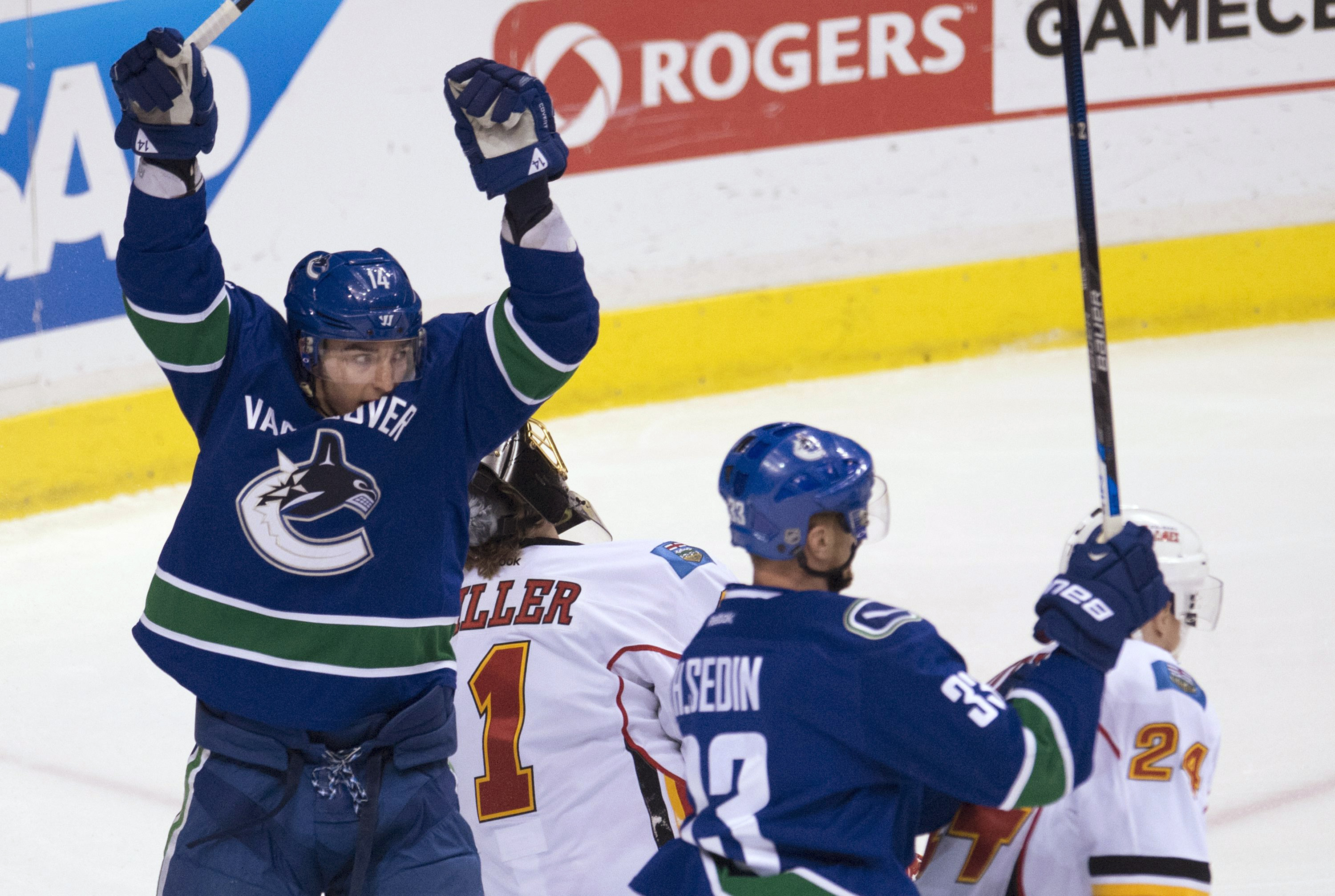 Vancouver Canucks left wing Alex Burrows (14) and Henrik Sedin (33) celebrate Daniel Sedin's goal against the Calgary Flames during the first period of Game 2 of an NHL hockey first-round playoff series, Friday, April 17, 2015, in Vancouver, British Colum
