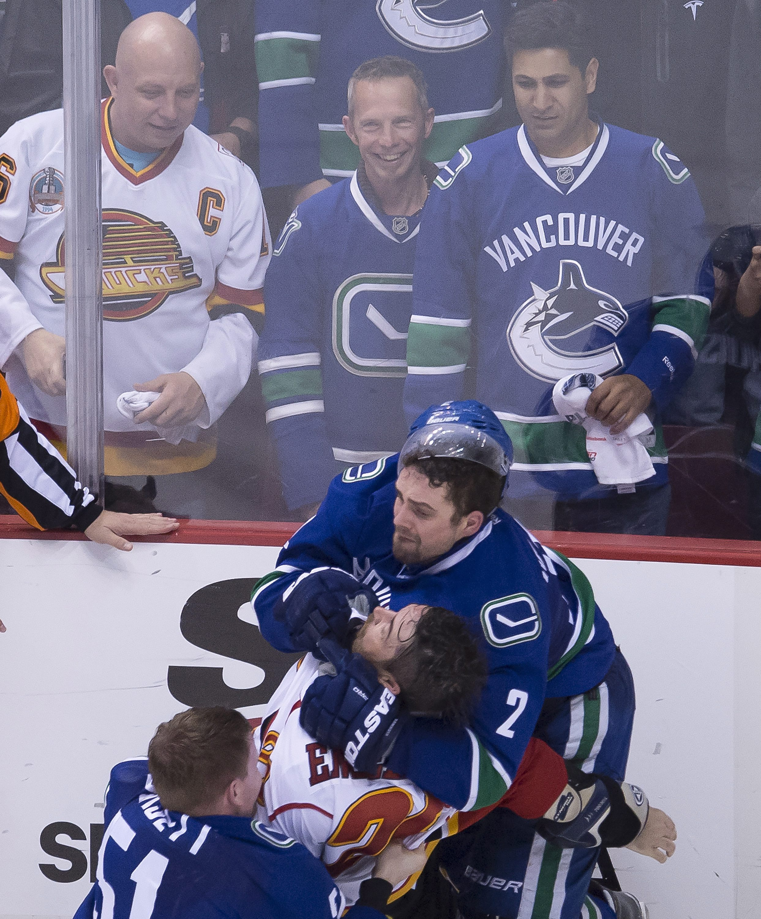 Vancouver Canucks' Derek Dorsett (51) and Dan Hamhuis (2) fight with Calgary Flames defenseman Deryk Engelland (29) during the third period of Game 2 of an NHL hockey first-round playoff series, Friday, April 17, 2015, in Vancouver, British Columbia. (Jon