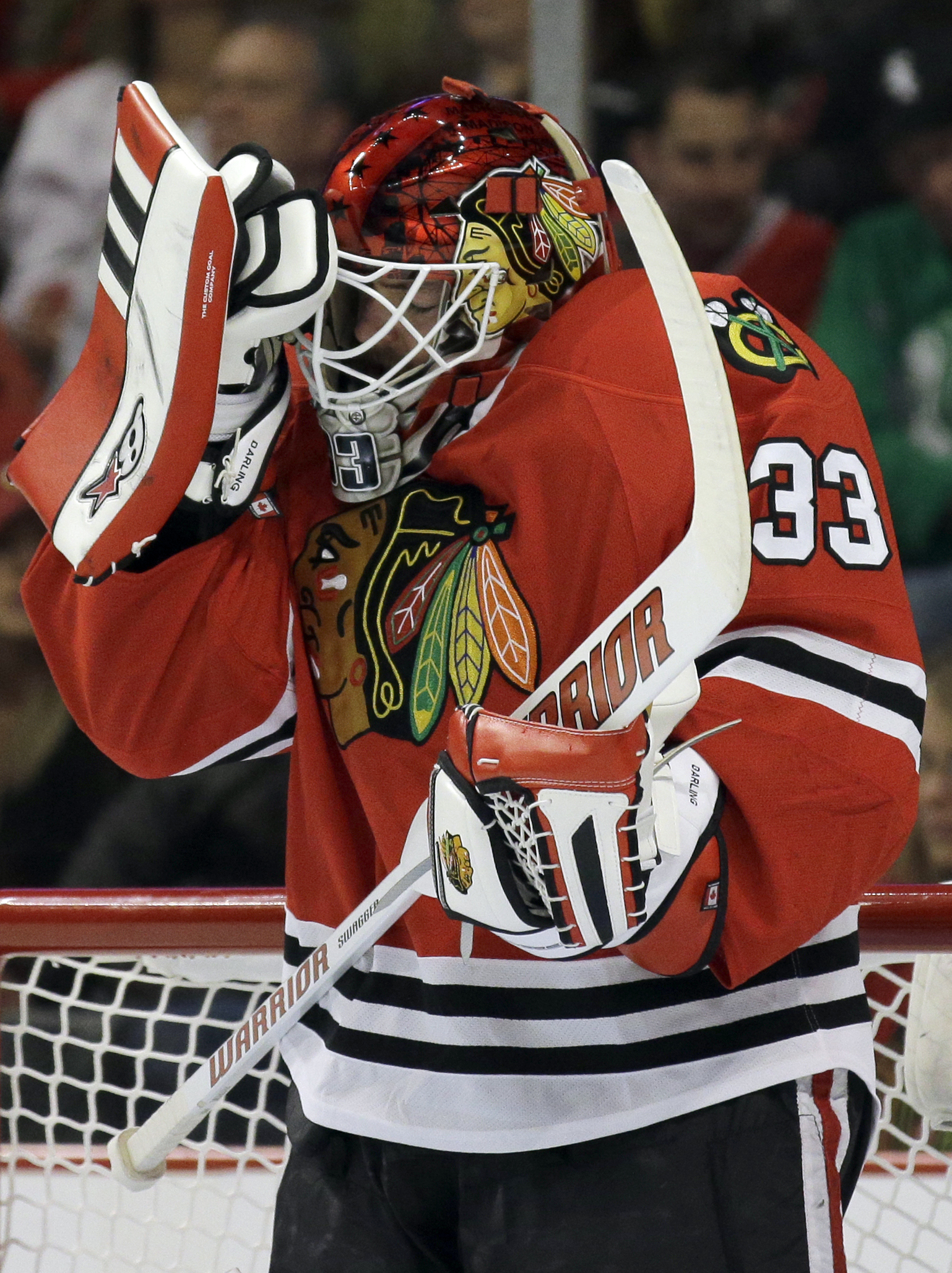 Chicago Blackhawks goalie Scott Darling checks his helmet during the first period in Game 3 of an NHL Western Conference hockey playoff series against the Nashville Predators Sunday, April 19, 2015, in Chicago. (AP Photo/Nam Y. Huh)