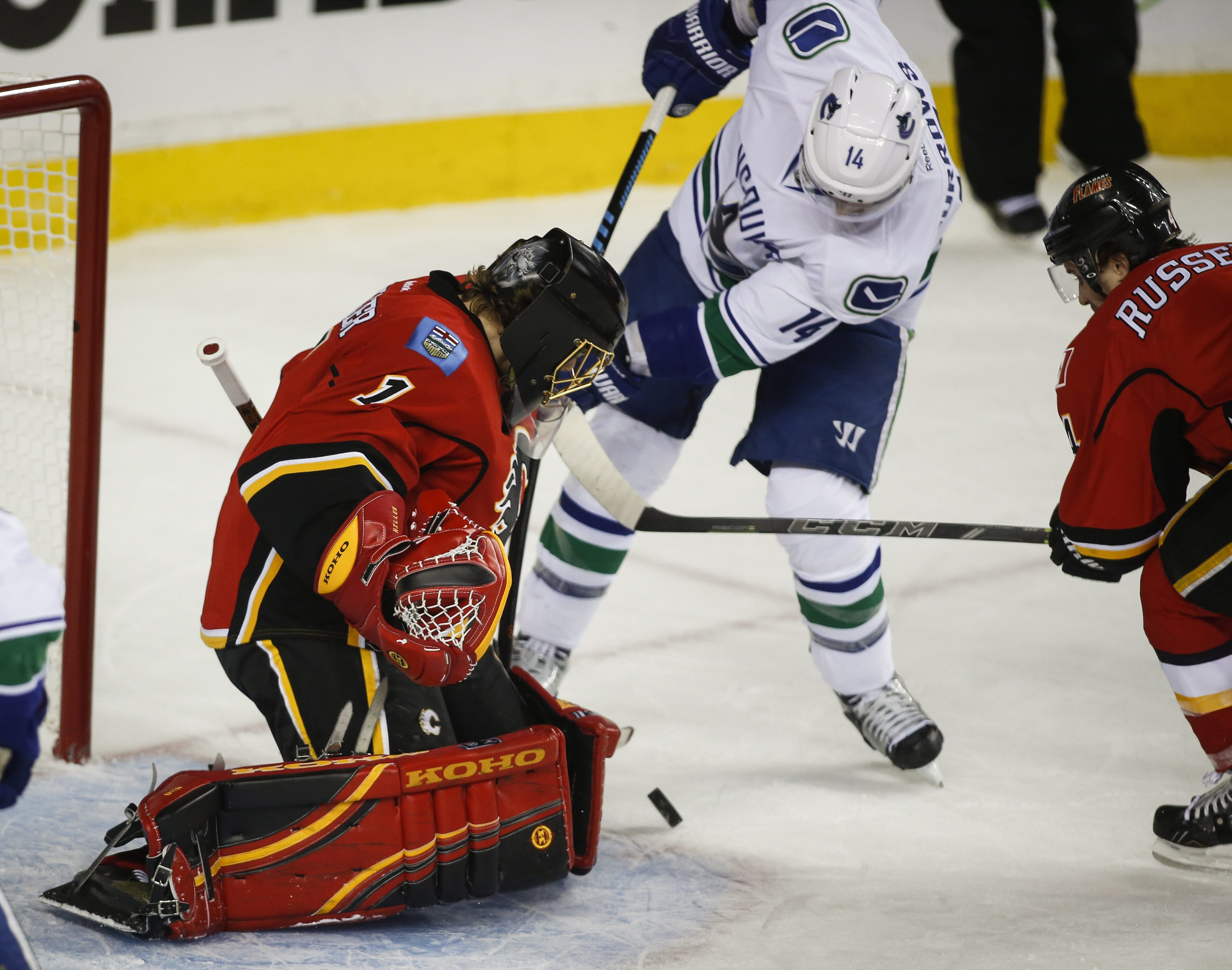 Vancouver Canucks' Alexandre Burrows, centre, tries to get the puck past Calgary Flames goalie Jonas Hiller, from Switzerland, during second period NHL first round playoff hockey action in Calgary, Sunday, April 19, 2015. (Jeff McIntosh/The Canadian Press