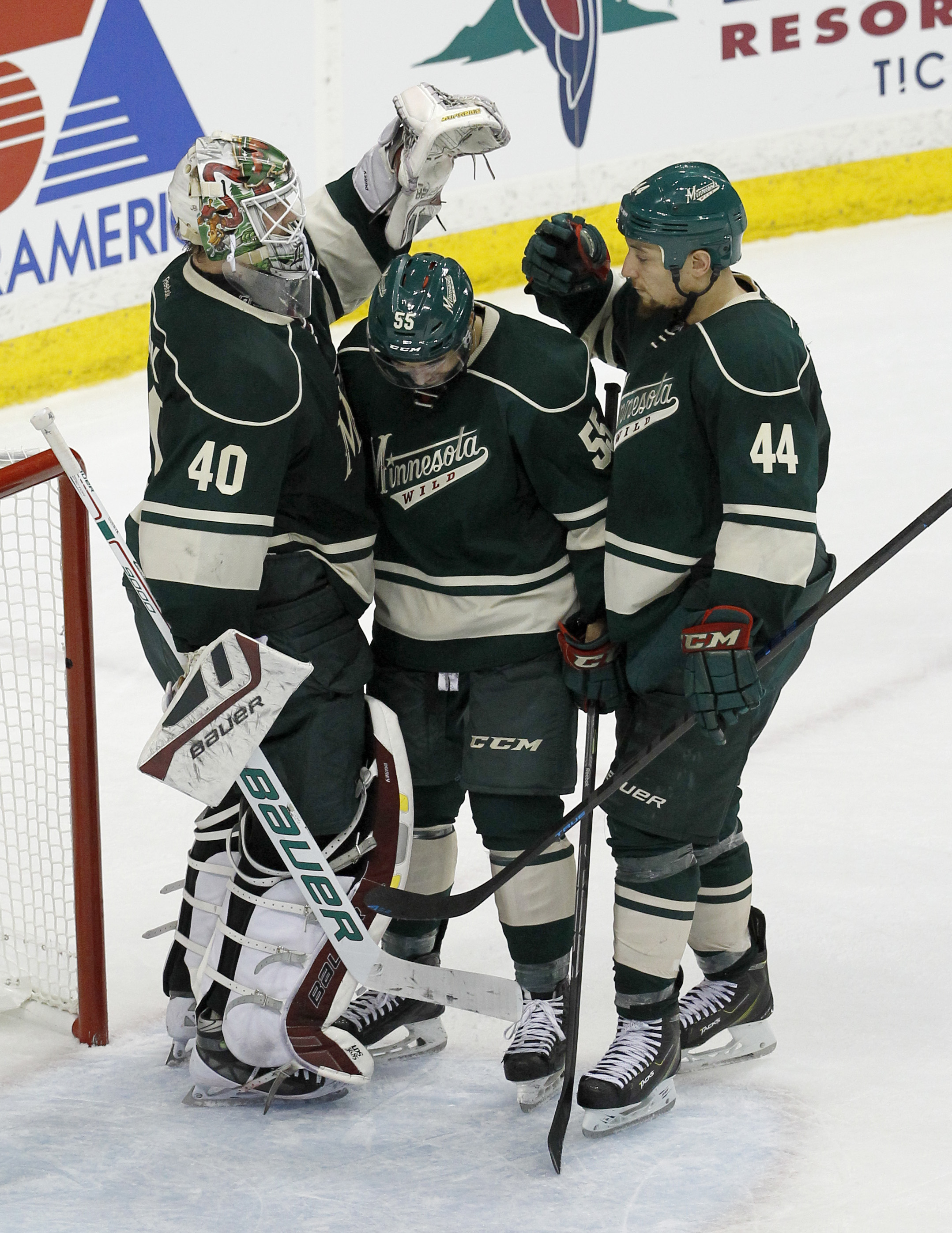 Minnesota Wild goalie Devan Dubnyk (40) celebrates with defenseman Matt Dumba, center, and right wing Chris Stewart (44) after the Wild defeated the St. Louis Blues 3-0 in Game 3 of an NHL hockey first-round playoff series game in St. Paul, Minn., Monday,