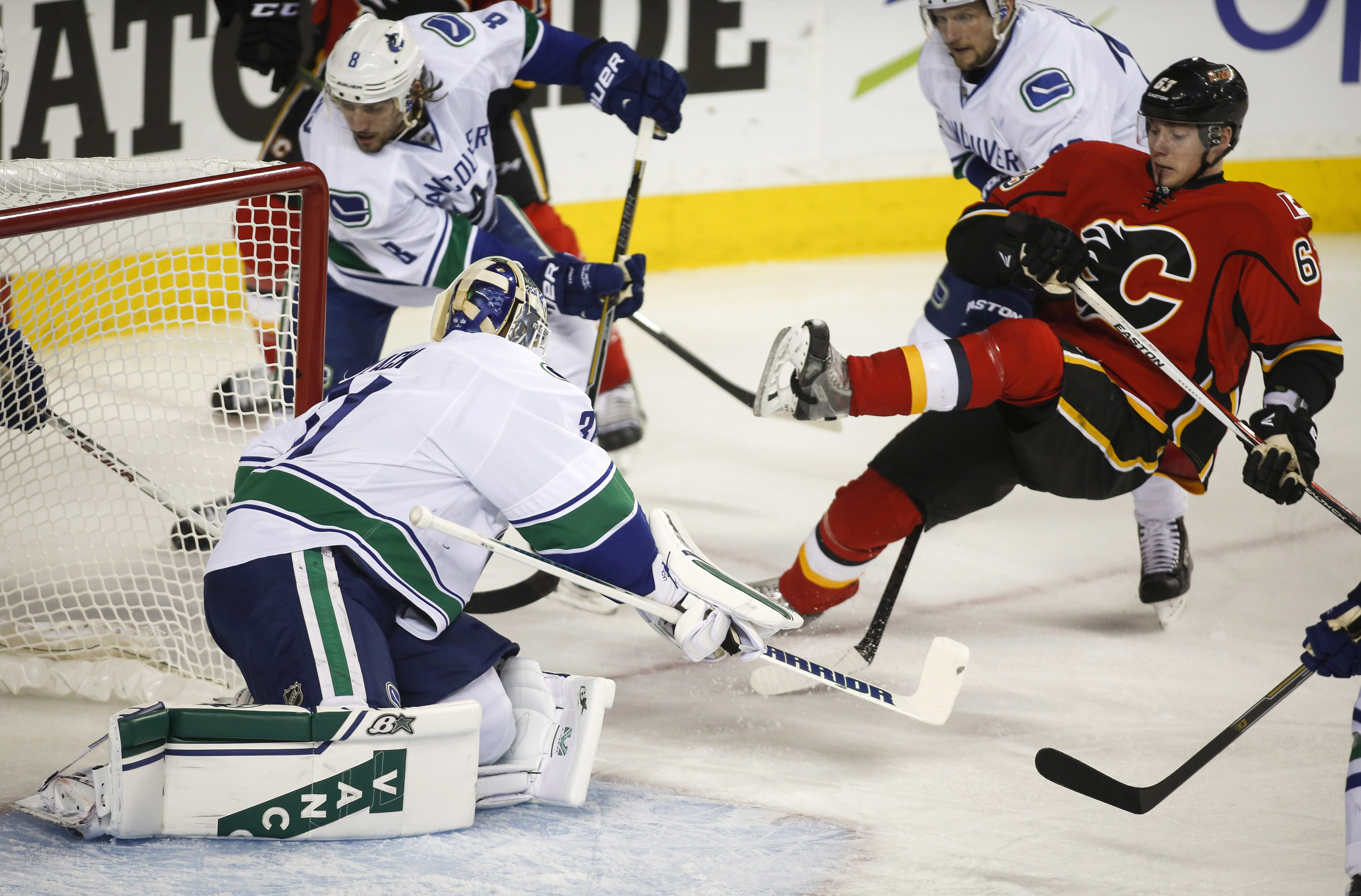 Vancouver Canucks goalie Eddie Lack, front left, protects the net as Calgary Flames' Sam Bennett gets hauled down in front of him during the first period of Game 4 of a first-round NHL hockey playoff series, Tuesday, April 21, 2015, in Calgary, Alberta. (