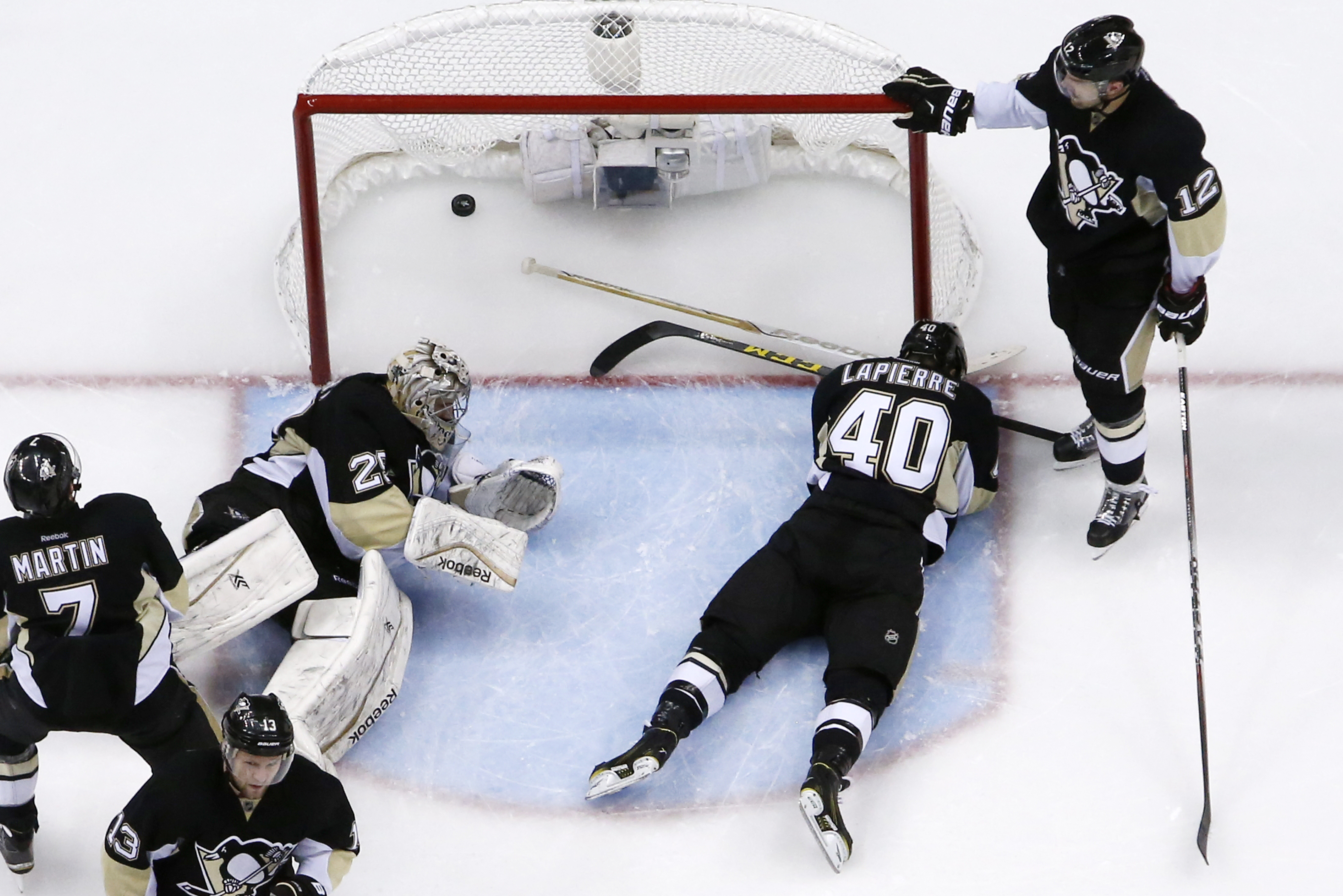 Pittsburgh Penguins goalie Marc-Andre Fleury (29) and Maxim Lapierre (40) lie in the goal crease with the overtime goal by New York Rangers' Kevin Hayes (13) in the net in overtime of a first-round NHL playoff hockey game in Pittsburgh on Wednesday, April
