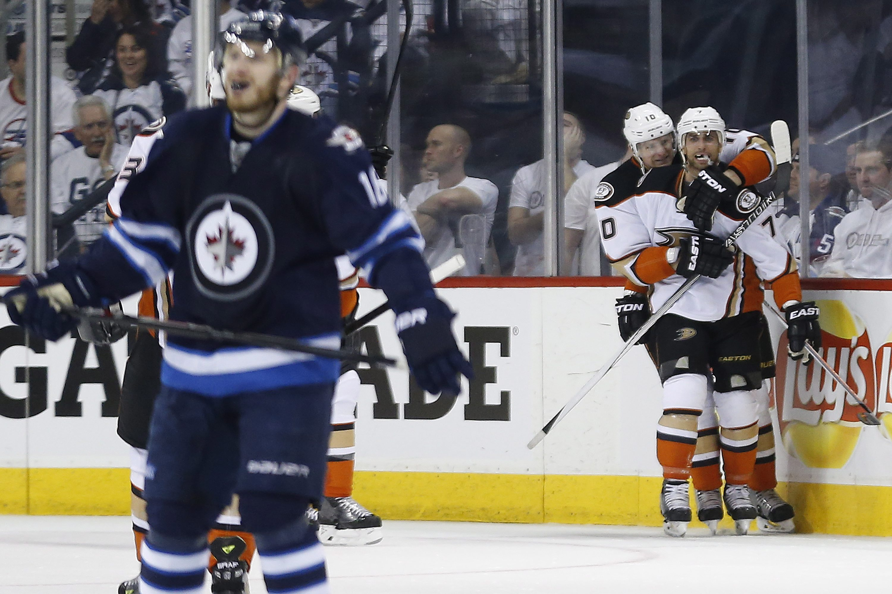 Anaheim Ducks' Andrew Cogliano (7) and Corey Perry (10) celebrate Cogliano's goal against the Winnipeg Jets during the second period of Game 4 of a first-round NHL hockey playoff series, Wednesday, April 22, 2015, in Winnipeg, Manitoba. (John Woods/The Ca