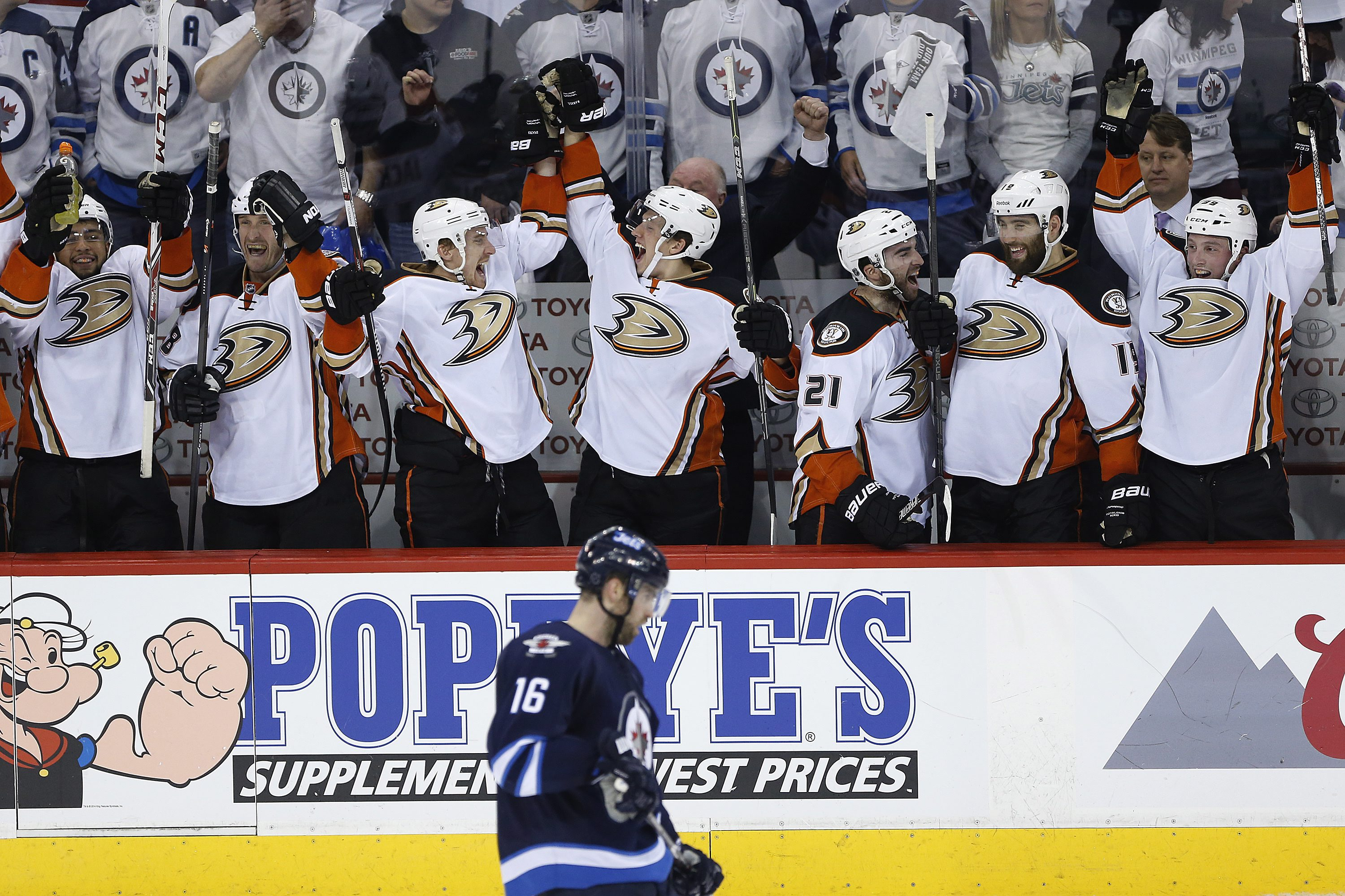 The Anaheim Ducks celebrate a goal against the Winnipeg Jets as Jets' Andrew Ladd (16) skates past during the third period of Game 4 of a first-round NHL hockey playoff series, Wednesday, April 22, 2015, in Winnipeg, Manitoba. Anaheim won 5-2 and swept th