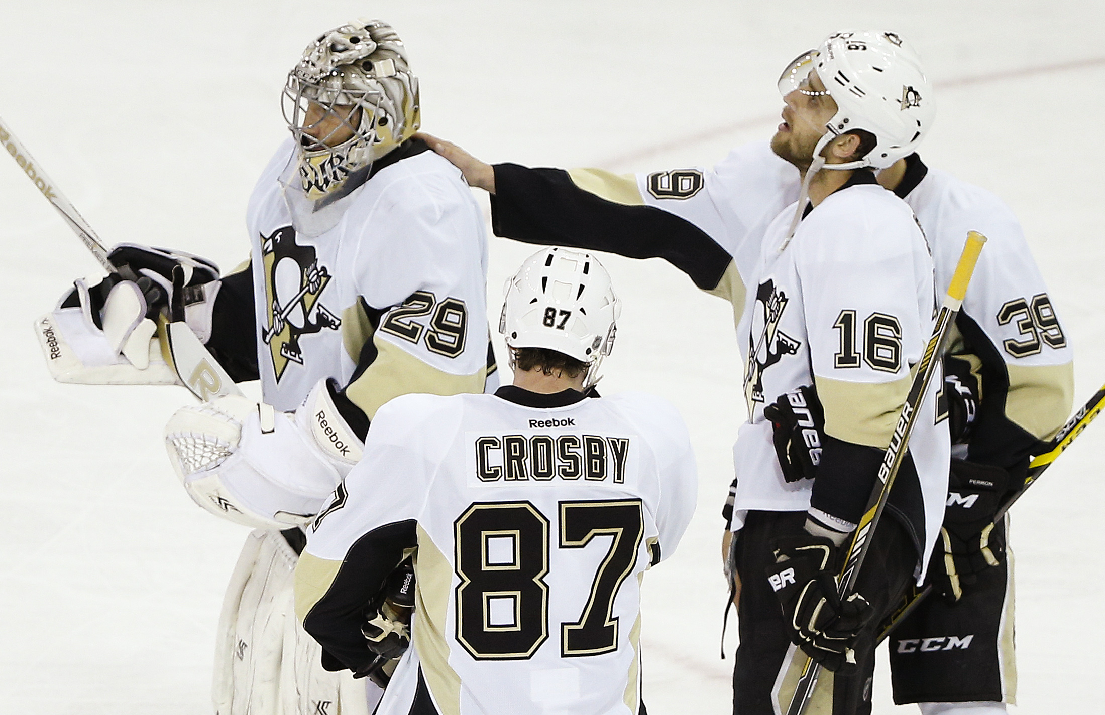 Pittsburgh Penguins goalie Marc-Andre Fleury (29) is consoled by center Brandon Sutter (16), left wing David Perron (39) and center Sidney Crosby (87) after the New York Rangers scored in overtime to win Game 5 in the first round of the NHL hockey Stanley