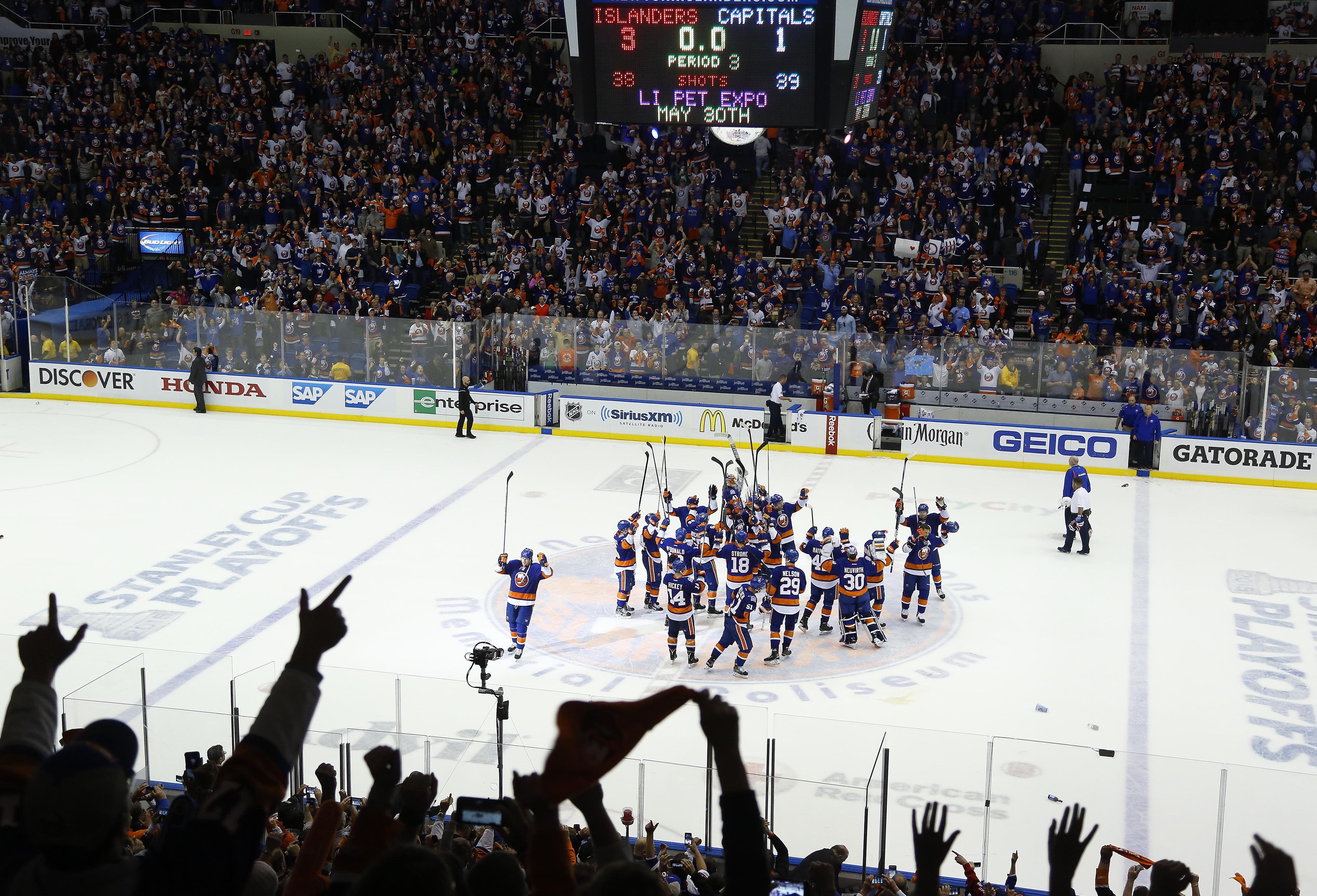 The New York Islanders celebrate at center ice after beating the Washington Capitals 3-1 in Game 6 in the first round of the NHL hockey Stanley Cup playoffs, Saturday, April 25, 2015, in Uniondale, N.Y. (AP Photo/Julie Jacobson)