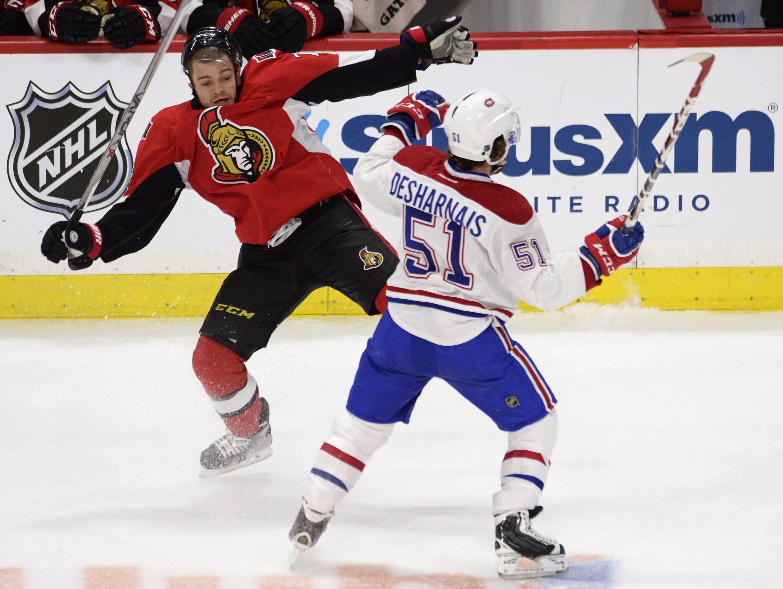 Montreal Canadiens' David Desharnais (51) collides with Ottawa Senators' Mark Borowiecki (74) during first period NHL playoff action in Ottawa, Ontario, Sunday, April 26, 2015. (Adrian Wyld/The Canadian Press via AP) MANDATORY CREDIT