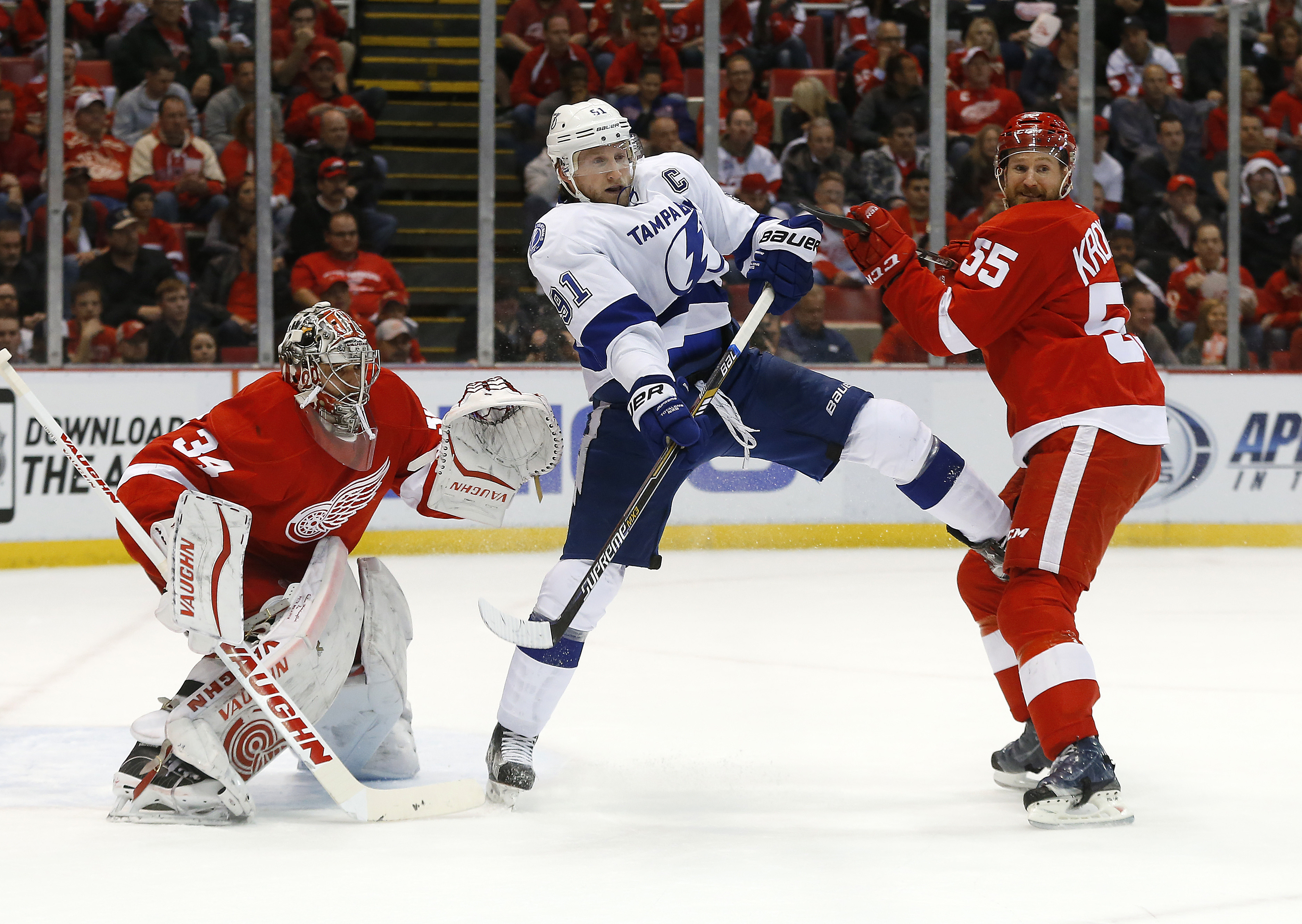 Tampa Bay Lightning center Steven Stamkos, middle, battles for position as Detroit Red Wings defenseman Niklas Kronwall (55) defends with goalie Petr Mrazek (34)in the first period of Game 6 of a first-round NHL Stanley Cup hockey playoff series in Detroi