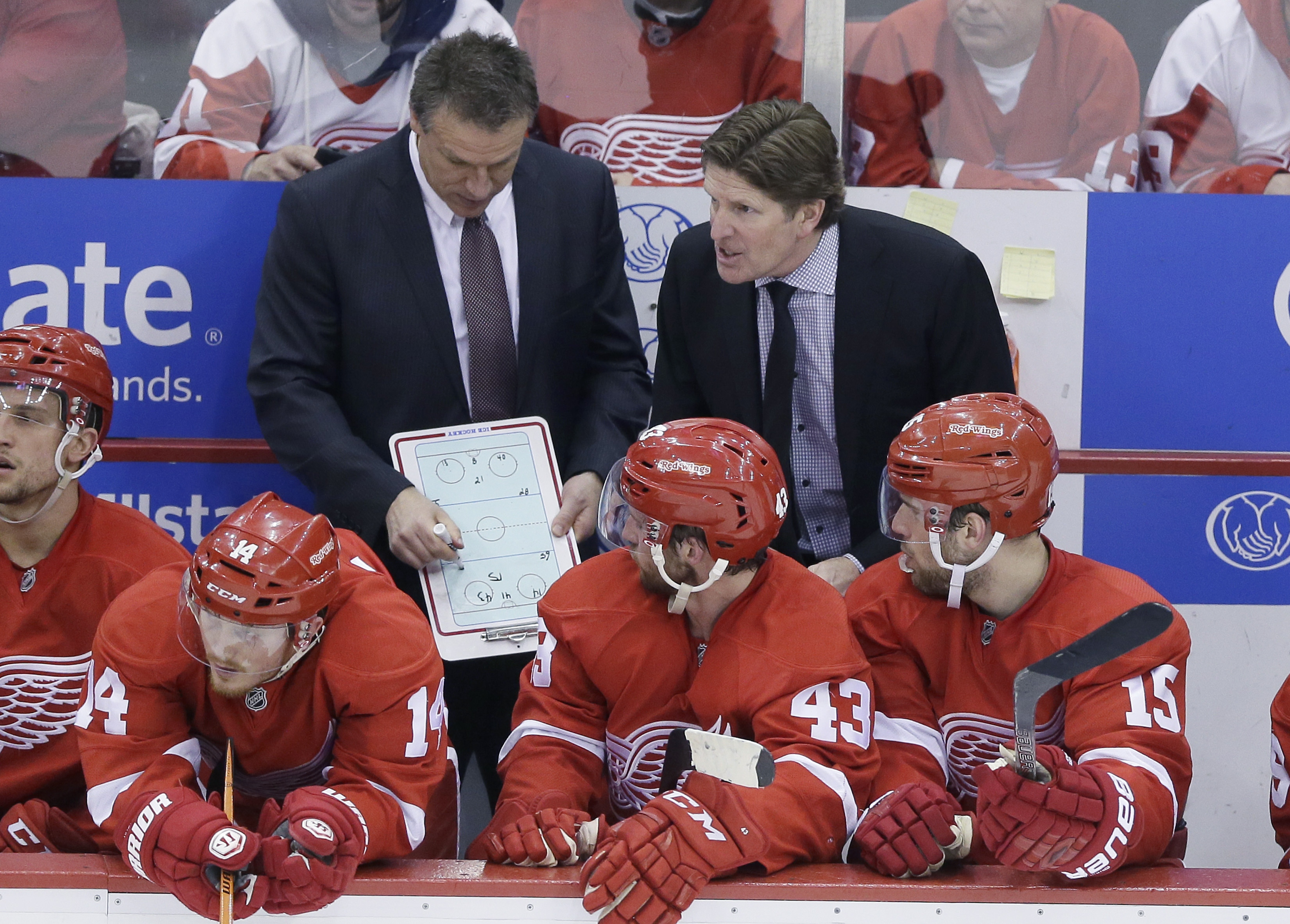 Detroit Red Wings head coach Mike Babcock right, talks to the team as assistant Andrew Brewer draws up a plan during the third period of Game 6 of a first-round NHL Stanley Cup hockey playoff series, Monday, April 27, 2015 in Detroit. The Lightning defeat