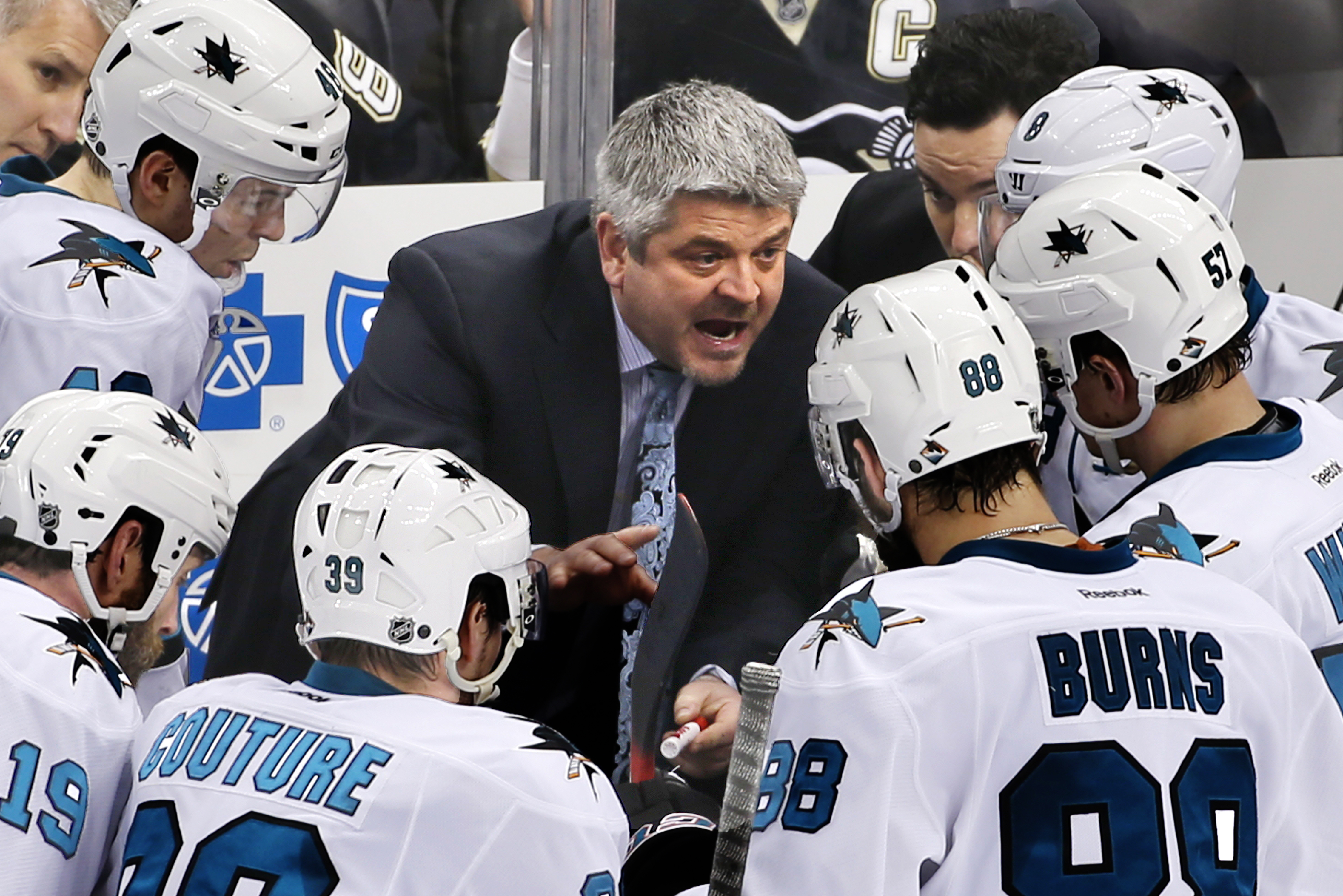 FILE - In this March 29, 2015, file photo, San Jose Sharks head coach Todd McLellan, center, talks to his team during a timeout in the third period of an NHL hockey game against the Pittsburgh Penguins in Pittsburgh.  The Sharks announced Monday, April 20