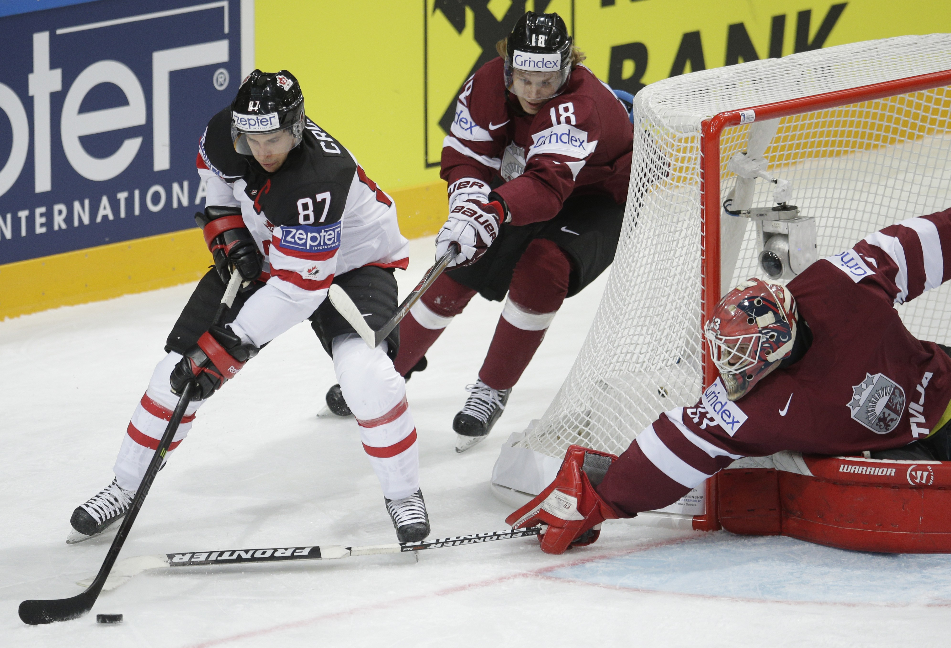 Canada's Sidney Crosby, left, controls a puck past Latvia's Rodrigo Abols, center, and Latvia's  Ervins Mustukovs, right, during the Hockey World Championships Group A in Prague, Czech Republic, Friday, May 1, 2015. (AP Photo/Petr David Josek)