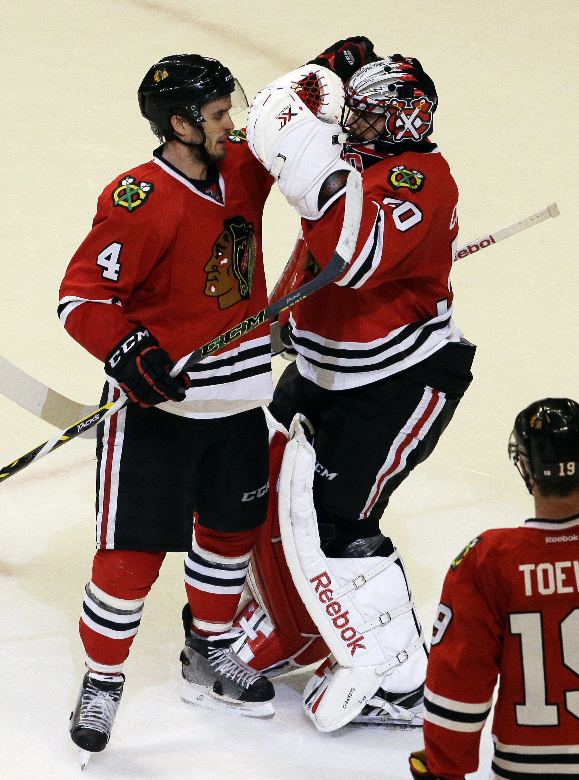 Chicago Blackhawks defenseman Niklas Hjalmarsson, left, celebrates with goalie Corey Crawford after the Blackhawks defeated the Minnesota Wild 4-3 during Game 1 in the second round of the NHL Stanley Cup hockey playoffs in Chicago, Friday, May 1, 2015. (A