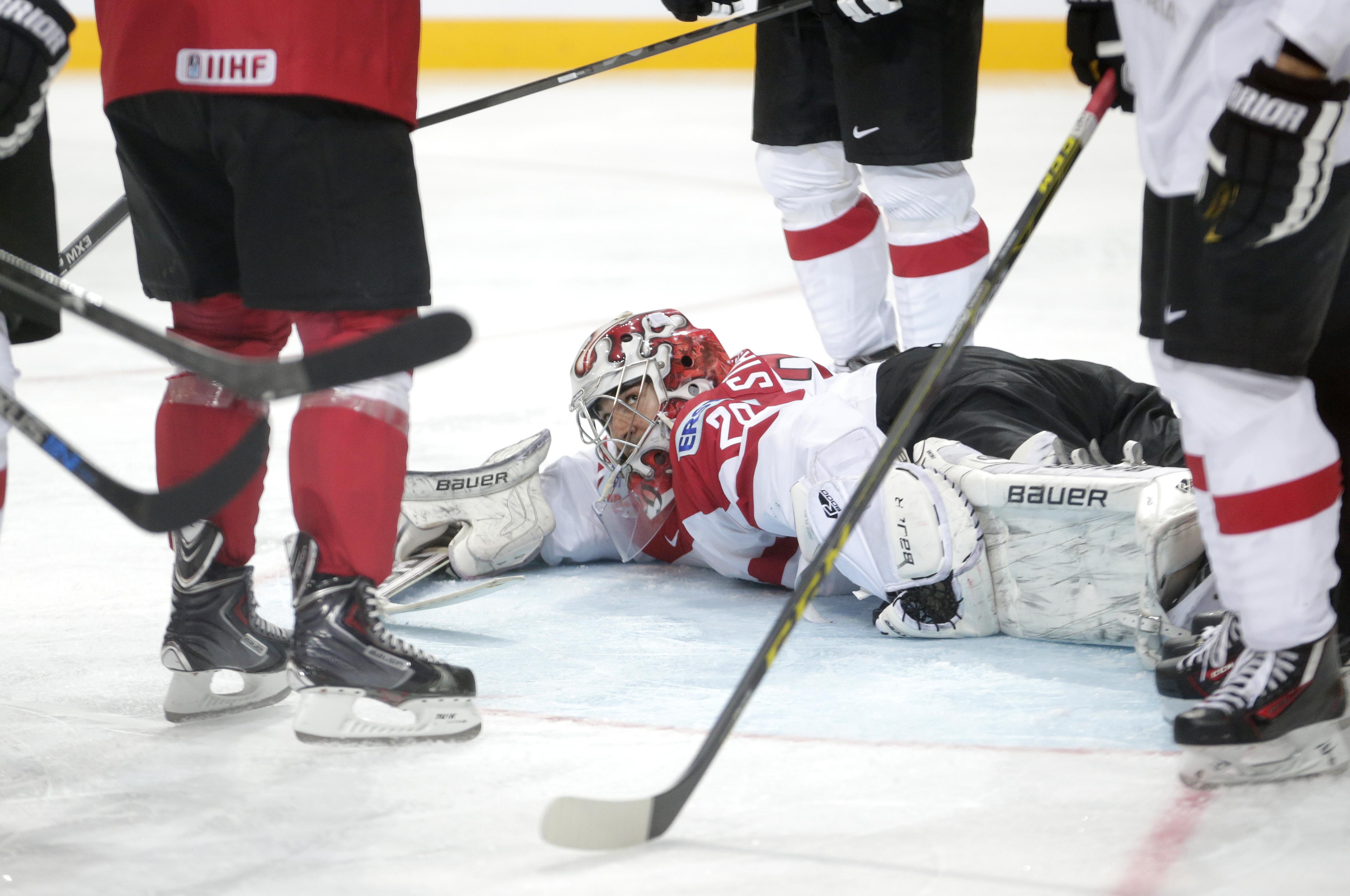 Austria's goalkeeper Bernhard Starkbaum lies on the ice during the Hockey World Championships Group A match against Switzerland in Prague, Czech Republic, Saturday, May 2, 2015. (AP Photo/Petr David Josek)