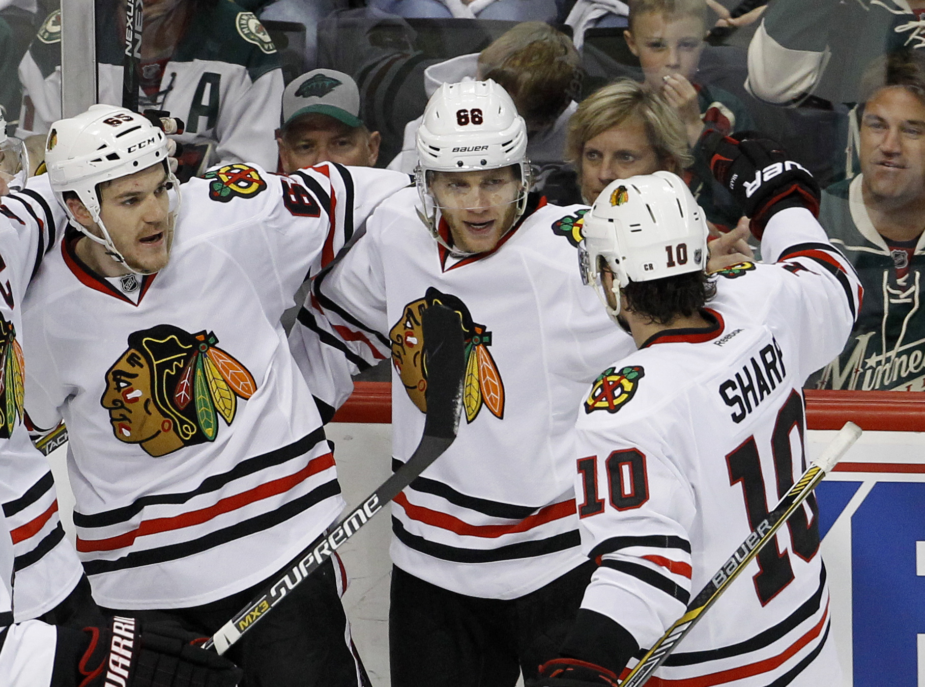 Chicago Blackhawks center Andrew Shaw, left, and left wing Patrick Sharp (10) congratulate right wing Patrick Kane (88) after he scored on Minnesota Wild goalie Devan Dubnyk during the first period of Game 3 in the second round of the NHL Stanley Cup hock