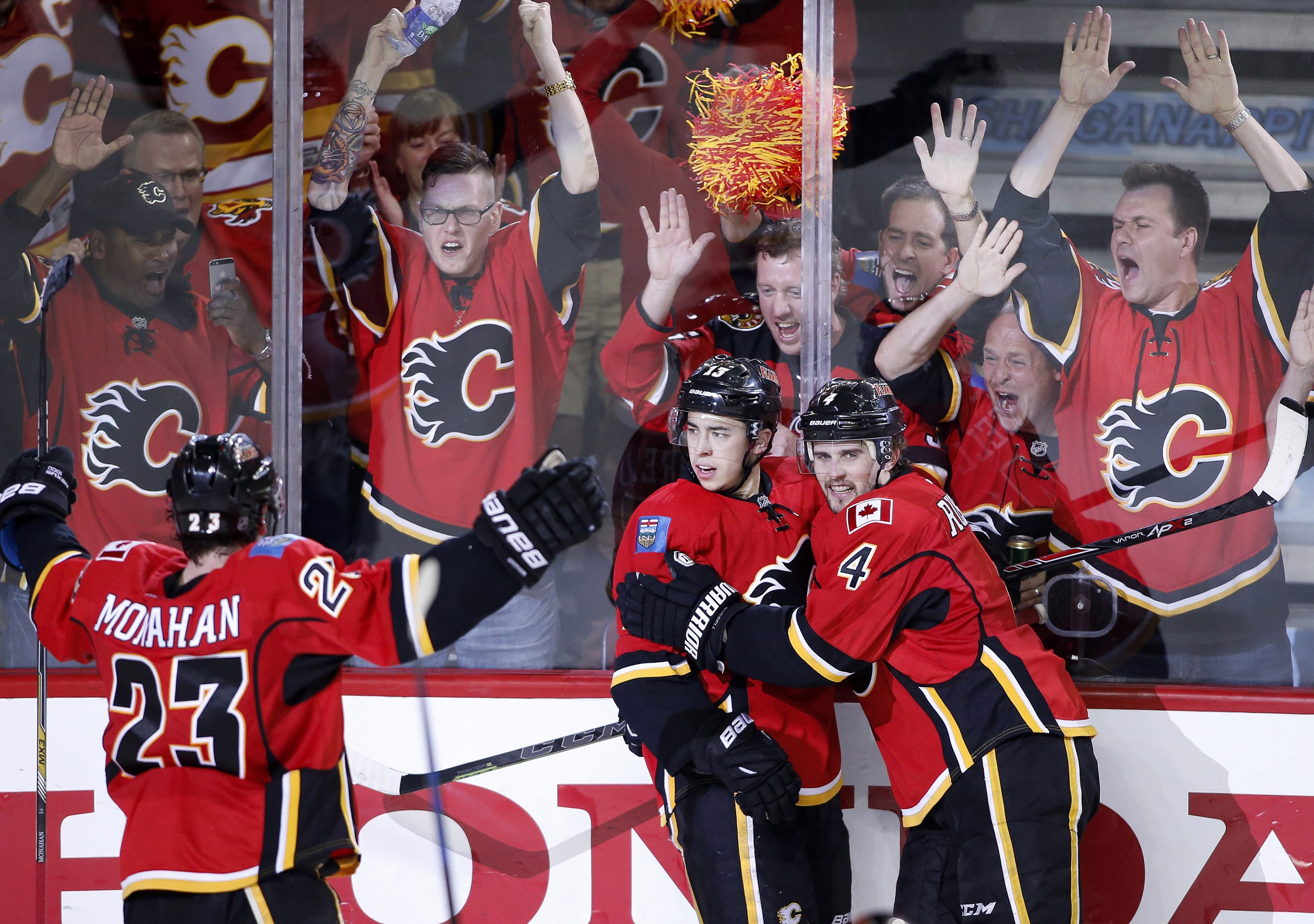 Calgary Flames' Johnny Gaudreau (13) celebrates his goal against the Anaheim Ducks with Sean Monahan (23) and Kris Russell (4) during the third period of Game 3 in the second round of the NHL Stanley Cup hockey playoffs, Tuesday, May 5, 2015, in Calgary,