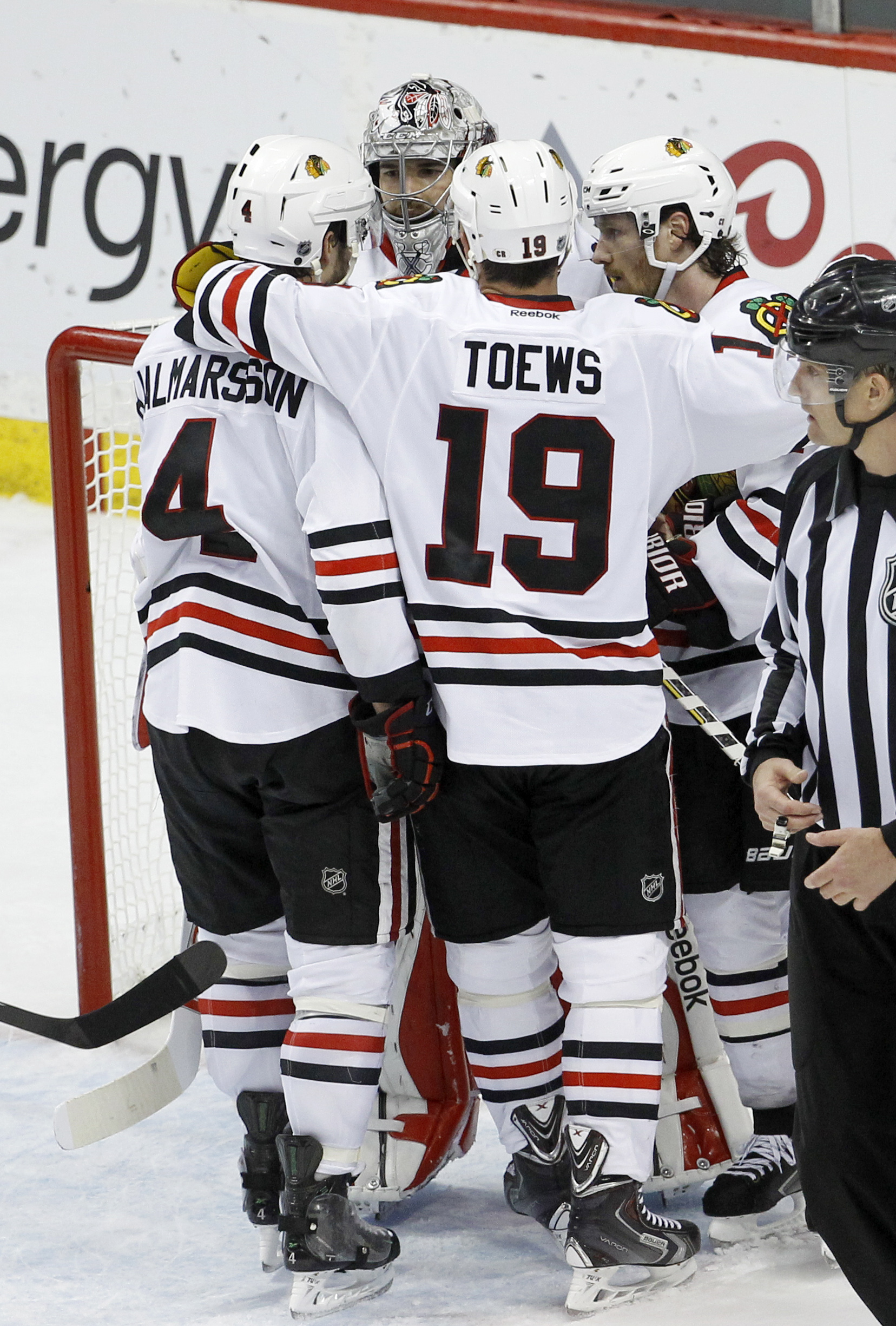Chicago Blackhawks center Jonathan Toews (19), defenseman Niklas Hjalmarsson, left, of Sweden, and defenseman Duncan Keith, right, congratulate goalie Corey Crawford after the Blackhawks defeated the Minnesota Wild 4-3 in Game 4 in the second round of the