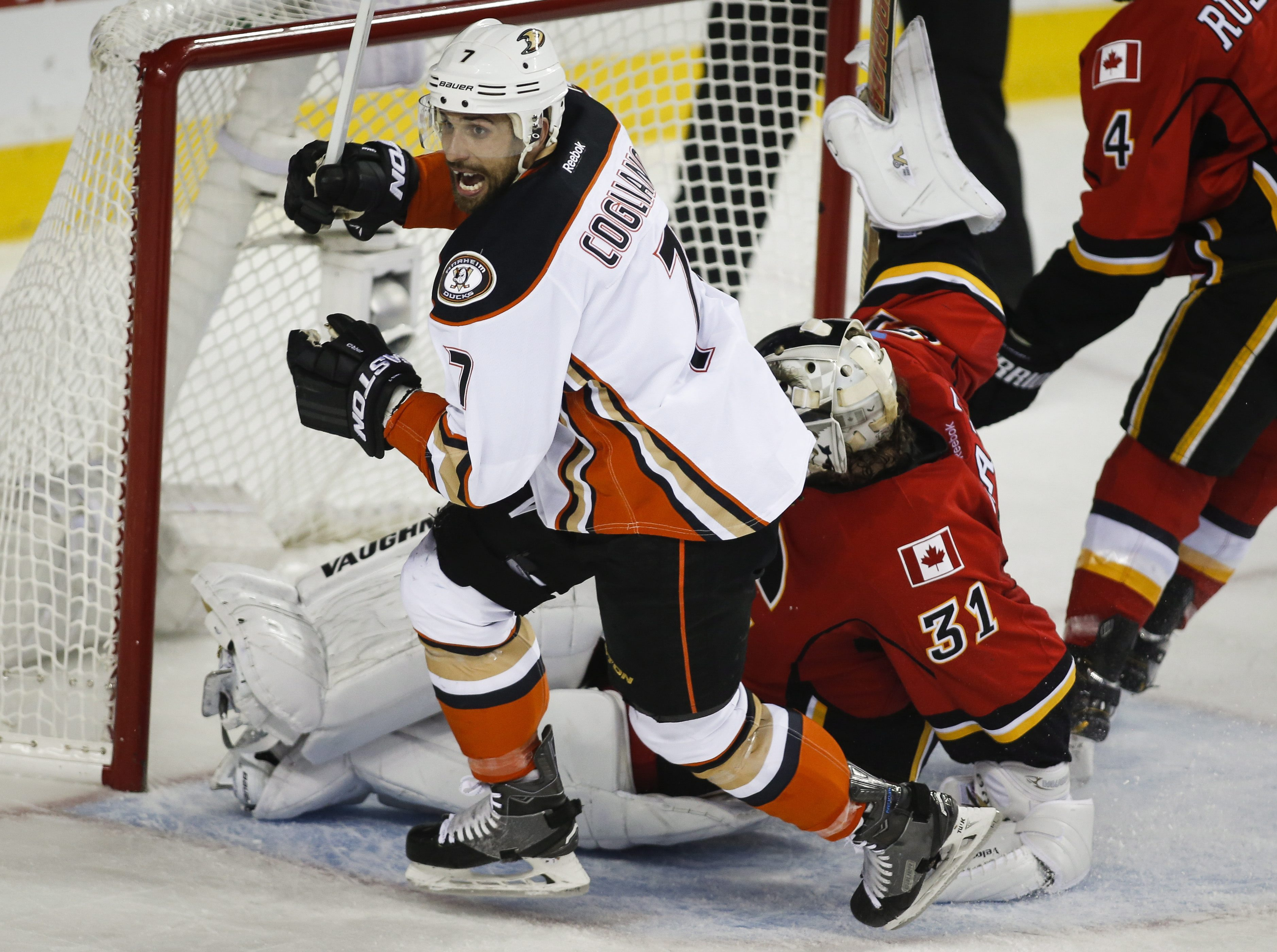 Anaheim Ducks' Andrew Cogliano, left, celebrates his tying goal as Calgary Flames goalie Karri Ramo, from Finland, picks himself up during the second period of Game 4 of NHL hockey second-round playoff action in Calgary, Alberta, Friday, May 8, 2015. (Jef
