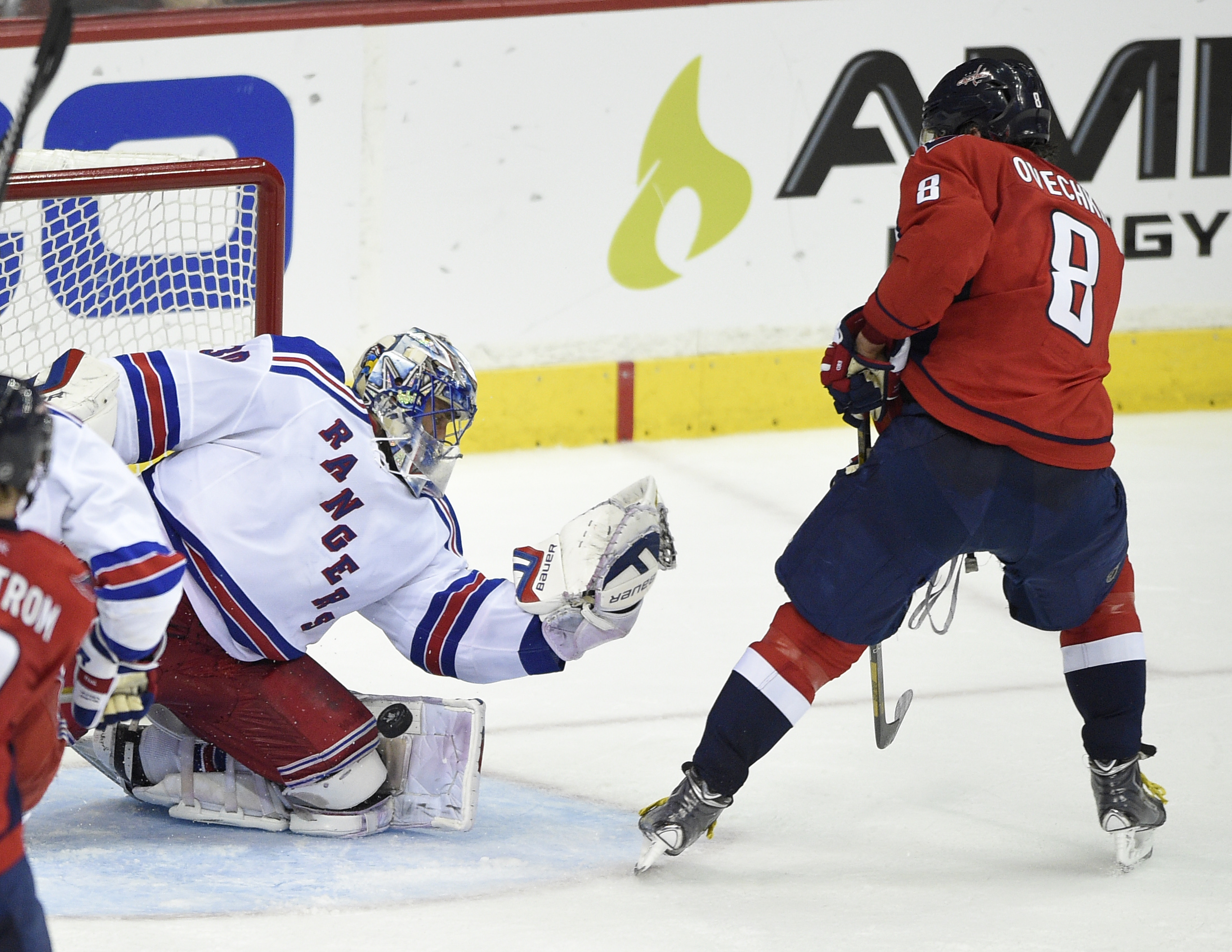 New York Rangers goalie Henrik Lundqvist (30), from Sweden, stops the puck against Washington Capitals left wing Alex Ovechkin (8), from Russia, during the third period of Game 6 in the second round of the NHL Stanley Cup hockey playoffs, Sunday, May 10,