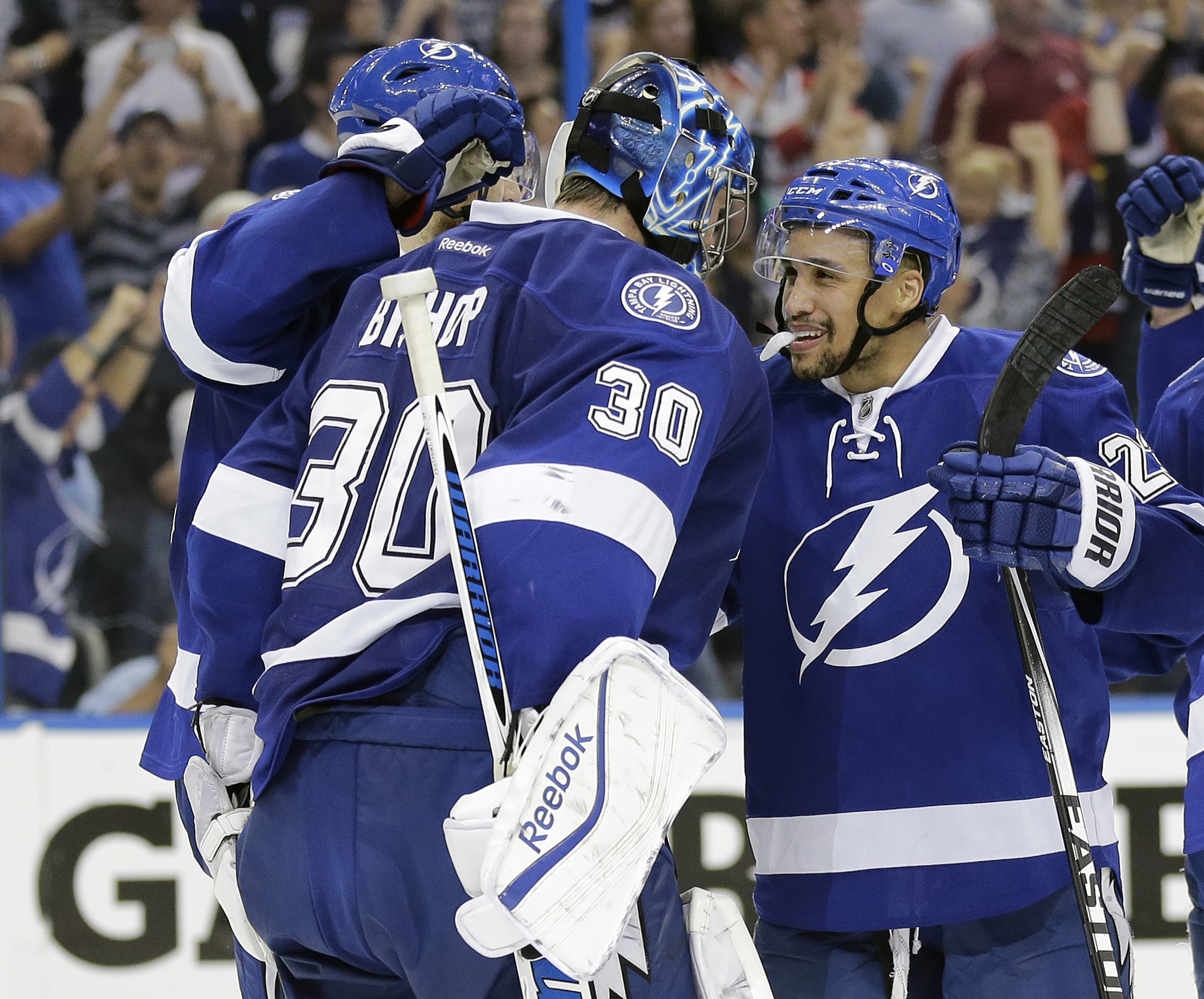 Tampa Bay Lightning goalie Ben Bishop (30) celebrates with right wing J.T. Brown (23) after the team defeated the Montreal Canadiens 4-1 during Game 6 of a second-round NHL Stanley Cup hockey playoff series Tuesday, May 12, 2015, in Tampa, Fla.  (AP Photo
