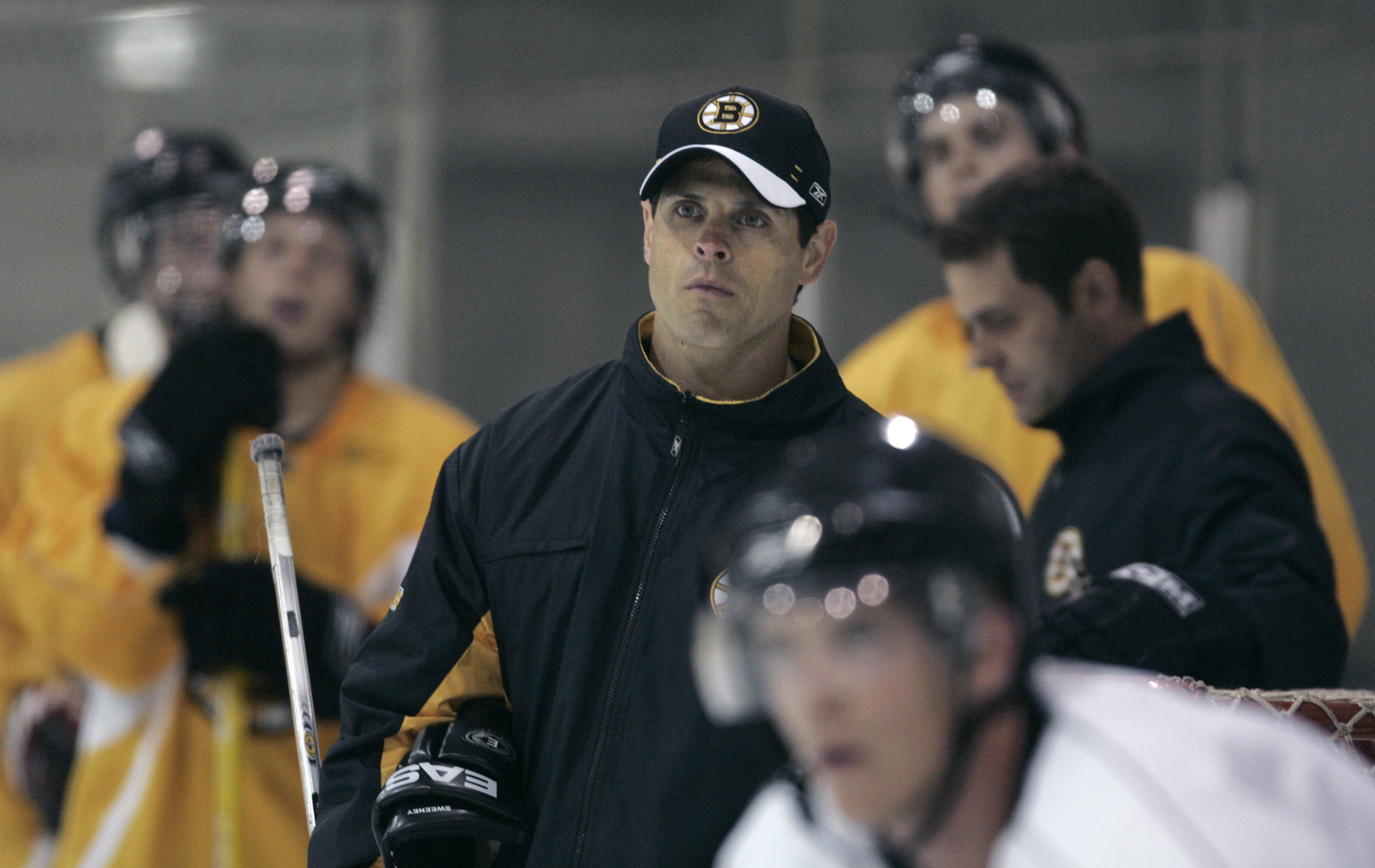 Boston Bruins director of player development Don Sweeney, center, watches play during a hockey team development camp in Wilmington, Mass. Monday, July 9, 2007.(AP Photo/Charles Krupa)