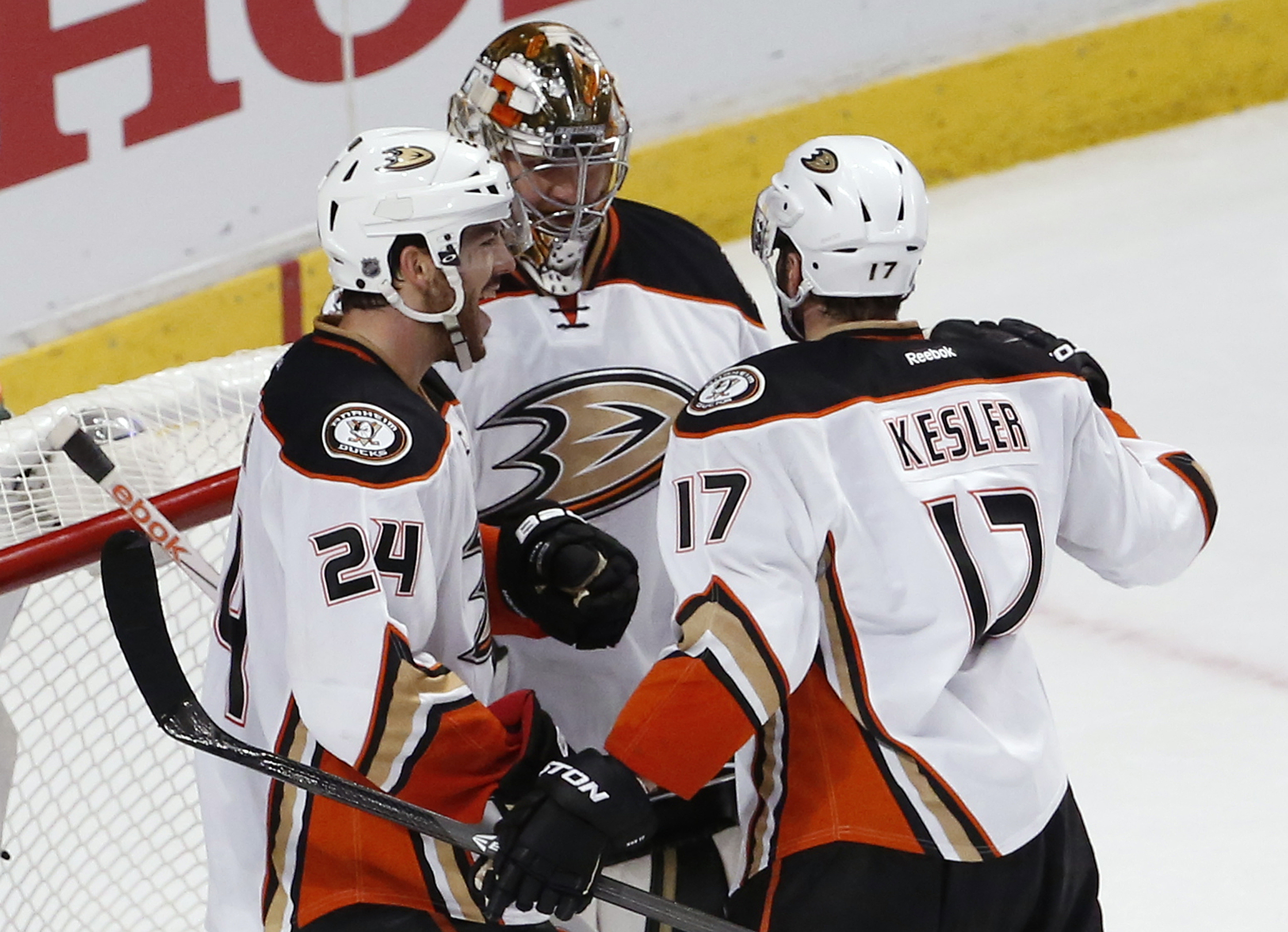 Anaheim Ducks defenseman Simon Despres (24) and center Ryan Kesler (17) celebrate with goalie Frederik Andersen after Game 3 of the Western Conference finals against the Chicago Blackhawks in the NHL hockey Stanley Cup playoffs, Thursday, May 21, 2015, in