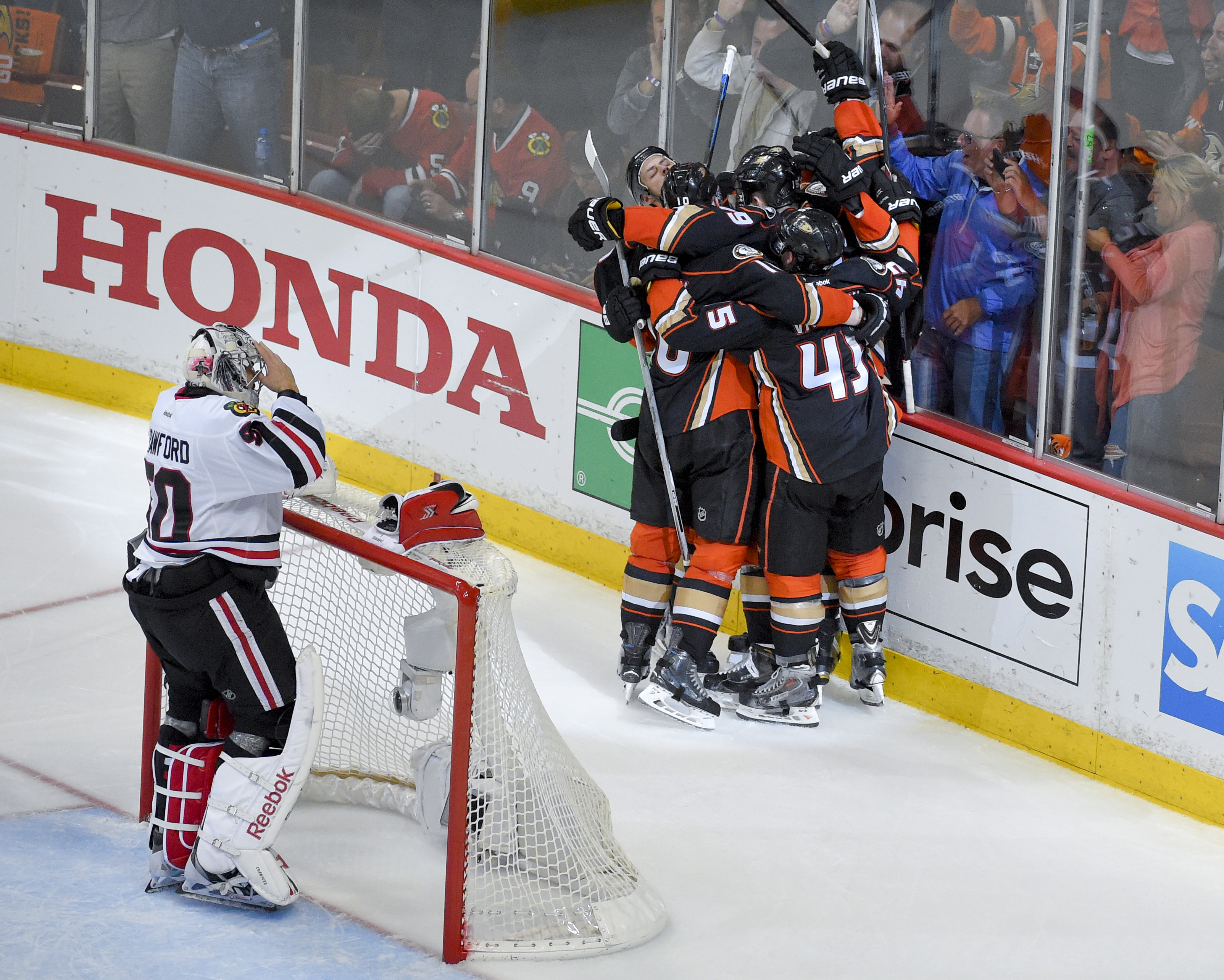 Members of the Anaheim Ducks celebrates Patrick Maroon's goal as Chicago Blackhawks goalie Corey Crawford looks on during the third period in Game 5 of the Western Conference final of the NHL hockey Stanley Cup playoffs in Anaheim, Calif., Monday, May 25,
