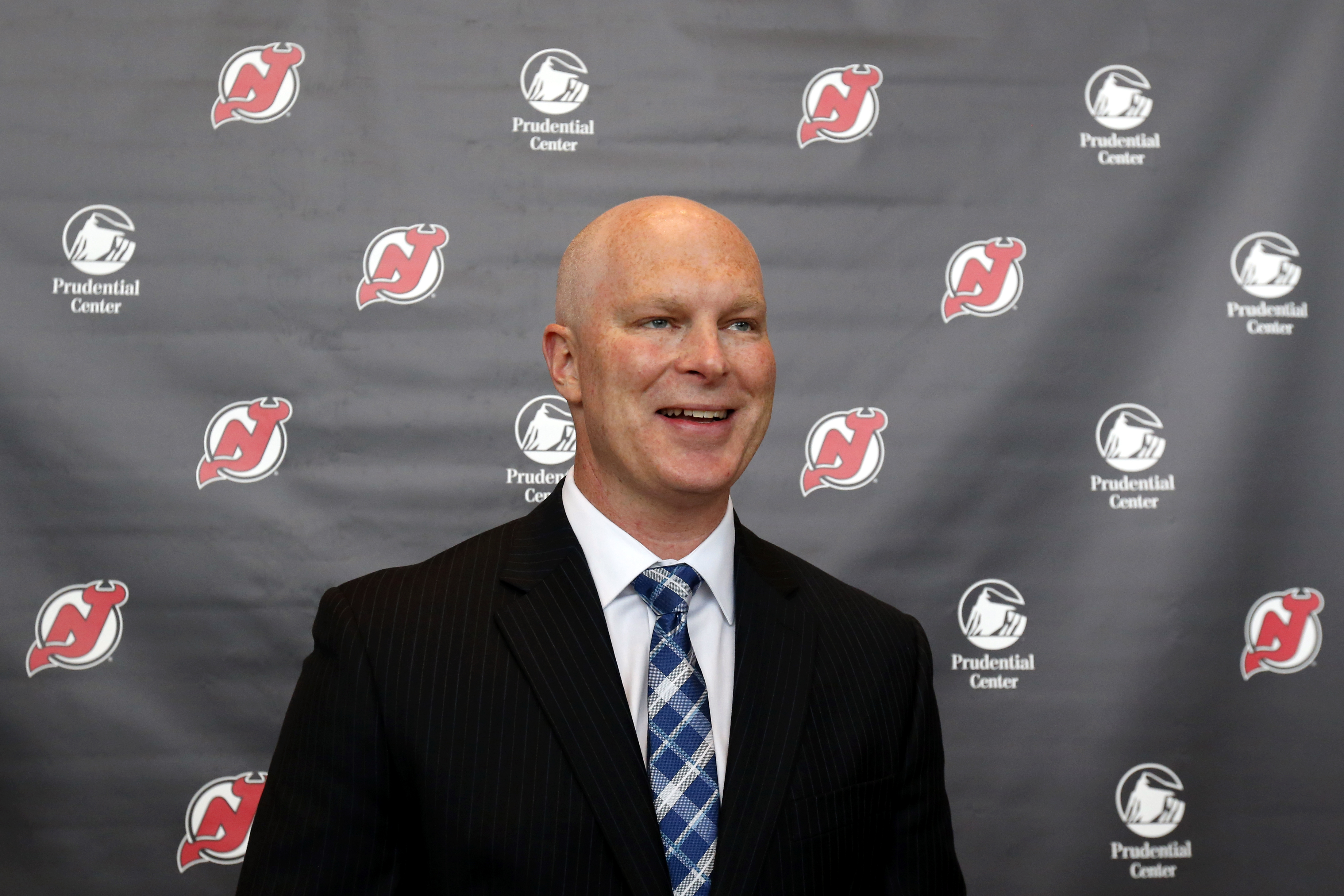 John Hynes smiles after being announced as the new head coach of the New Jersey Devils during an NHL hockey news conference, Tuesday, June 2, 2015, in Newark, N.J. (AP Photo/Julio Cortez)