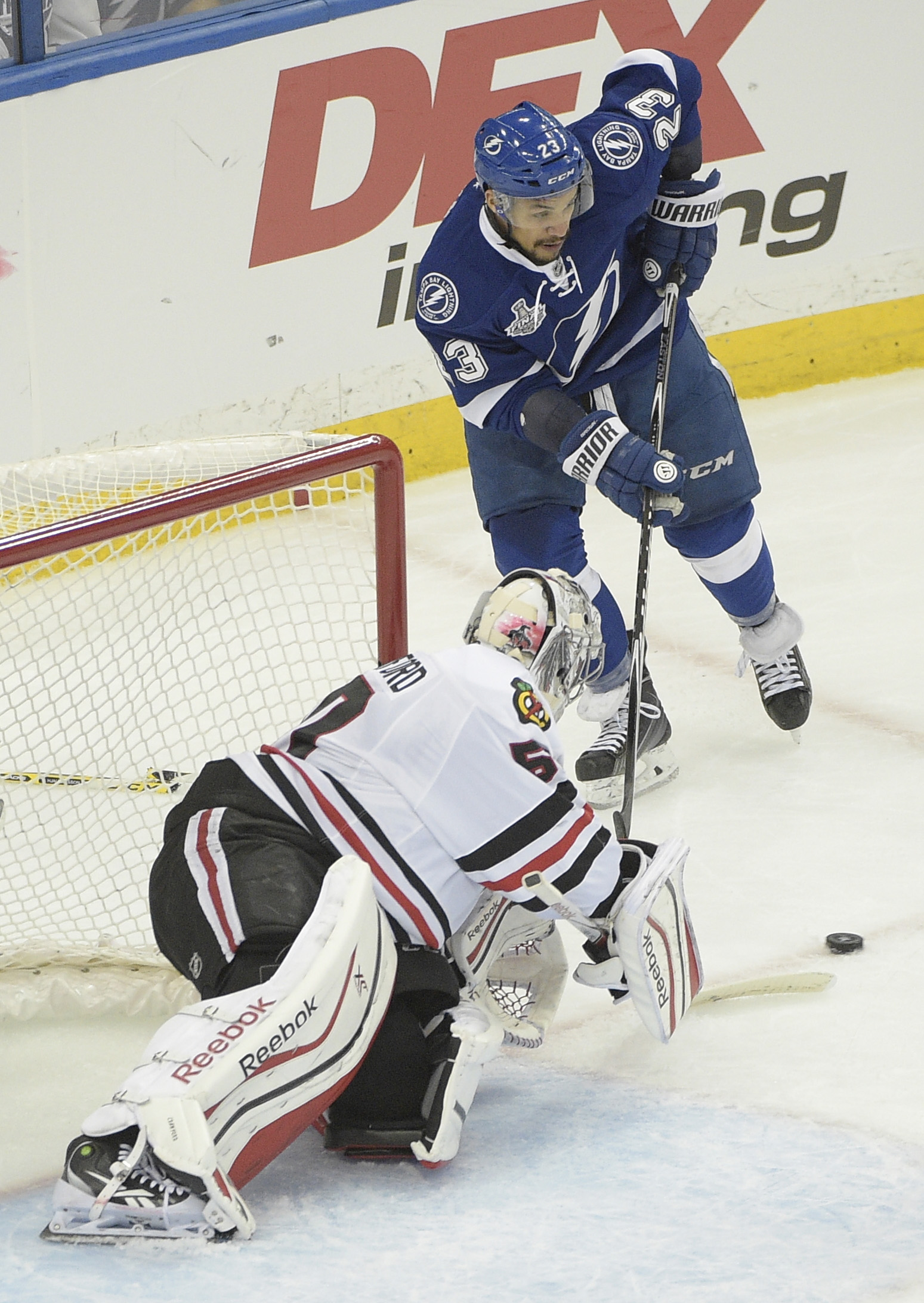 Chicago Blackhawks goalie Corey Crawford (50) , bottom, blocks a shot by Tampa Bay Lightning right wing J.T. Brown (23) during the first period in Game 1 of the NHL hockey Stanley Cup Final in Tampa, Fla., Wednesday, June 3, 2015.  (AP Photo/Phelan M. Ebe