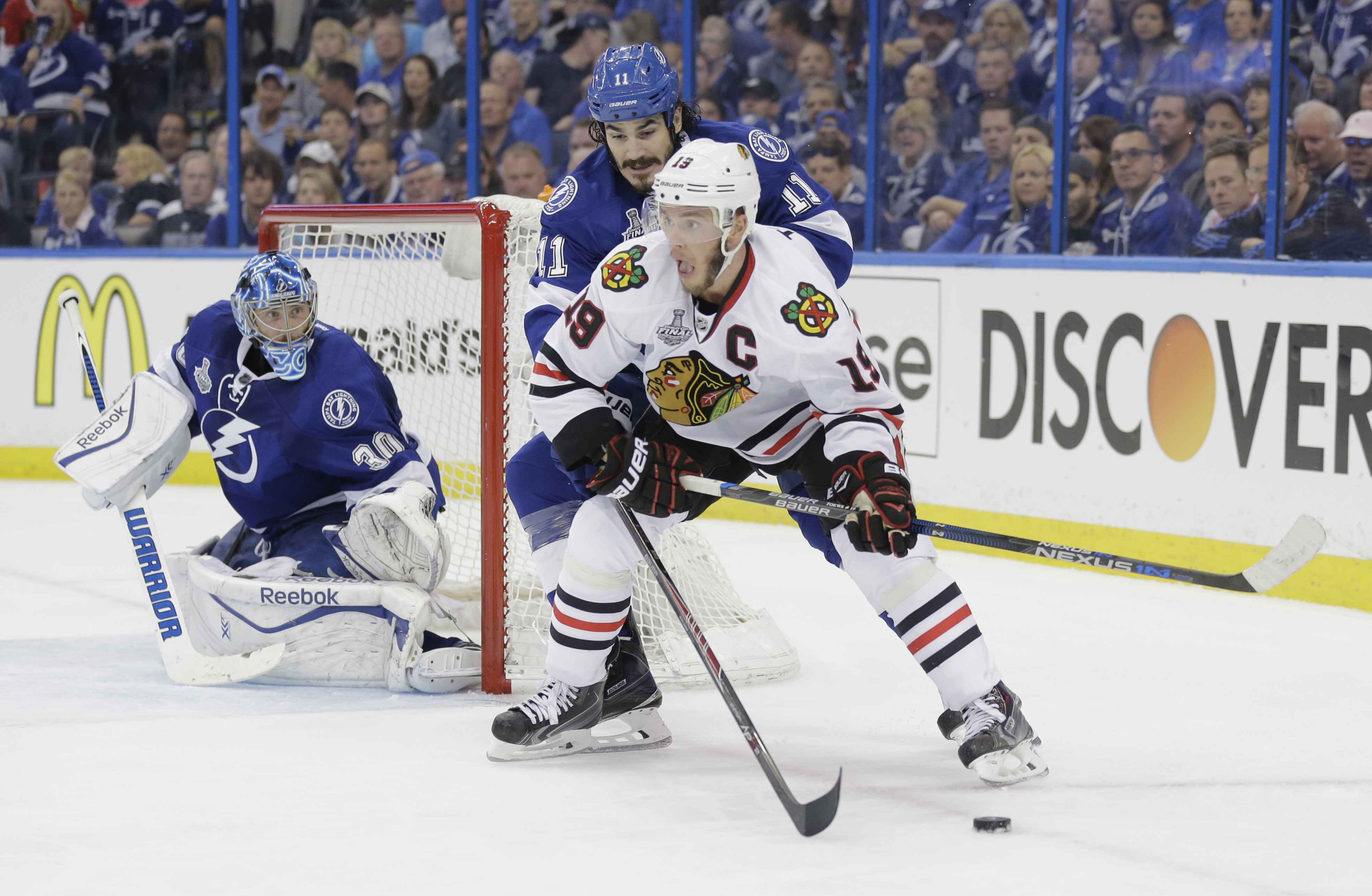 Chicago Blackhawks center Jonathan Toews (19), front, skates around Tampa Bay Lightning center Brian Boyle (11) as goalie Ben Bishop (50), left, defends the net, during the second period in Game 1 of the NHL hockey Stanley Cup Final in Tampa, Fla., Wednes