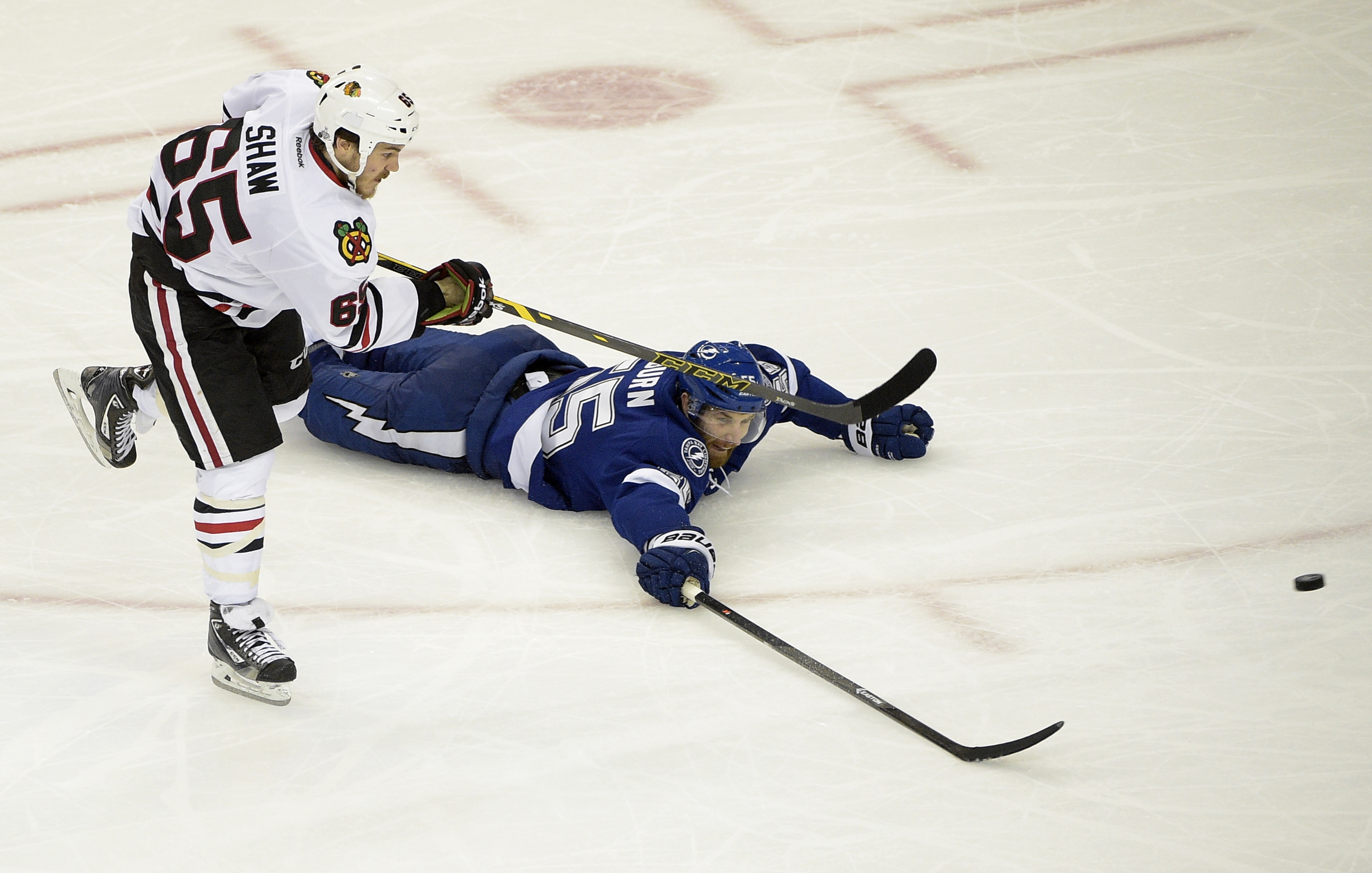 Chicago Blackhawks center Andrew Shaw (65) of Canada, left, shoots past Tampa Bay Lightning defenseman Braydon Coburn (55) of Canada,  during the third period in Game 1 of the NHL hockey Stanley Cup Final in Tampa, Fla., Wednesday, June 3, 2015. The Black