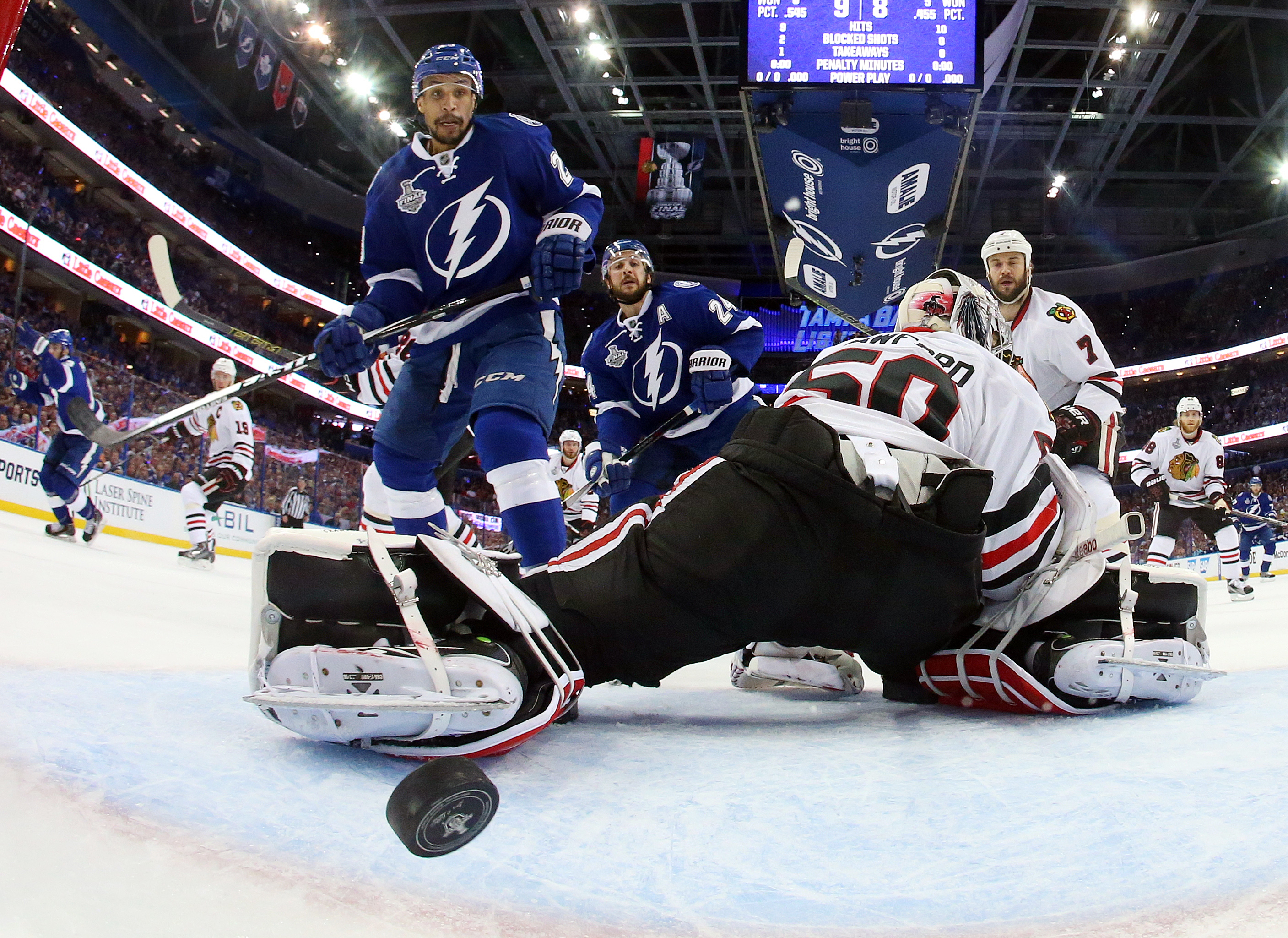 Tampa Bay Lightning right wing J.T. Brown, left, watches as Cedric Paquette's shot goes by Chicago Blackhawks goalie Corey Crawford during the first period in Game 2 of the NHL hockey Stanley Cup Final in Tampa, Fla., Saturday, June 6, 2015. (Bruce Bennet
